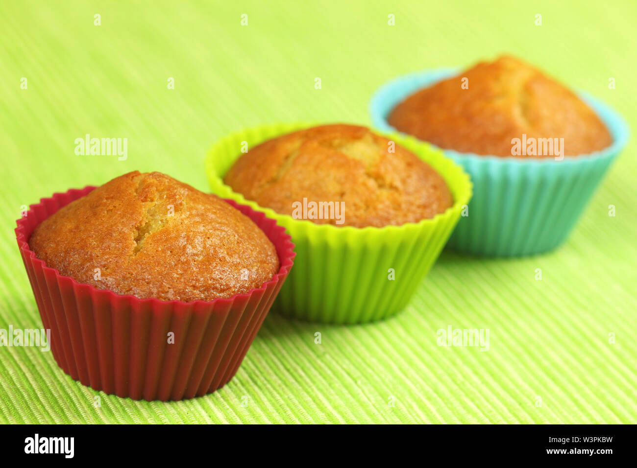 Three lemon cupcakes in colorful silicone moulds on green background - Stock Image