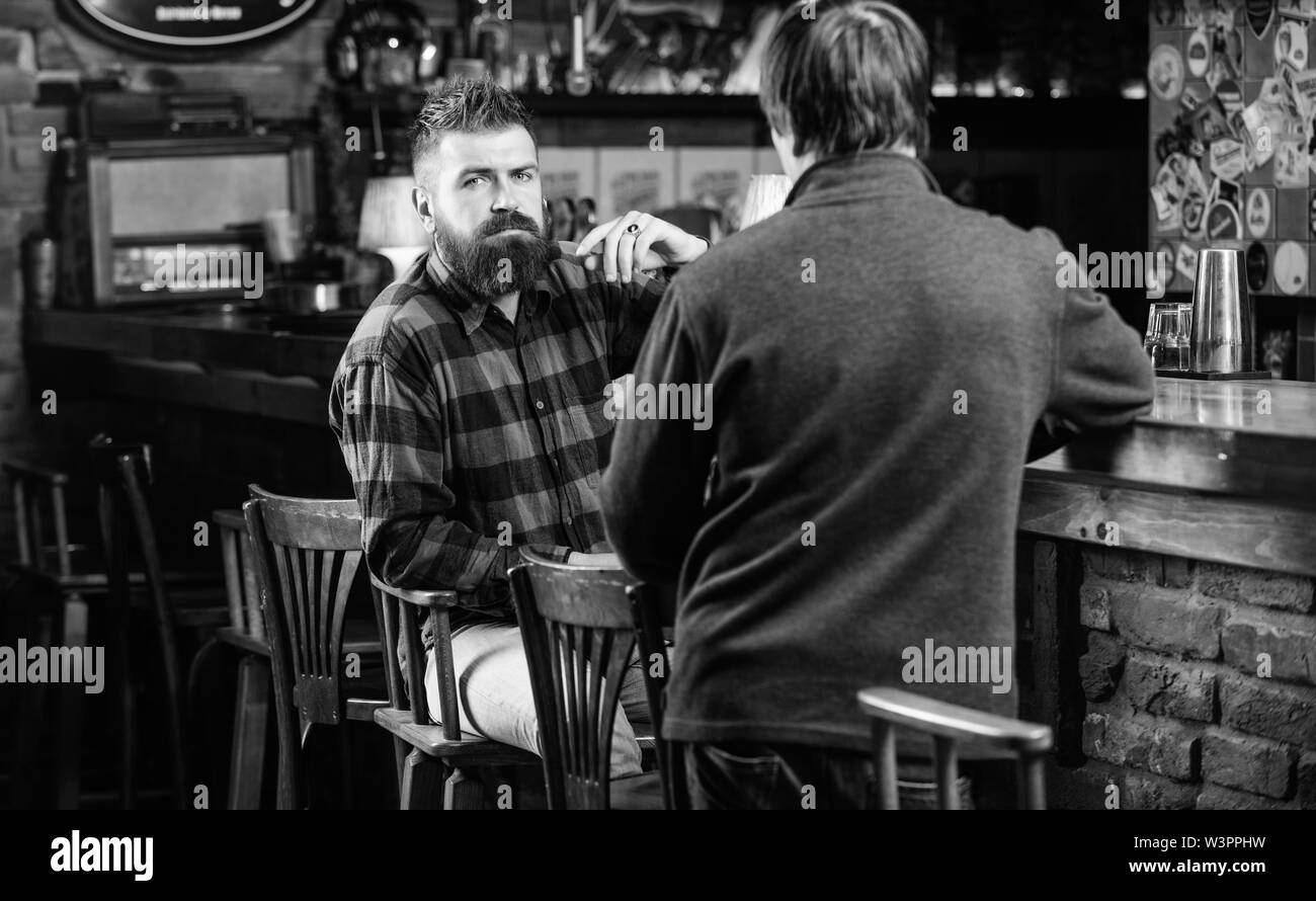 Interesting conversation. Men relaxing at bar. Friendship and leisure. Friday relaxation in bar. Friends relaxing in bar or pub. Hipster brutal bearde - Stock Image