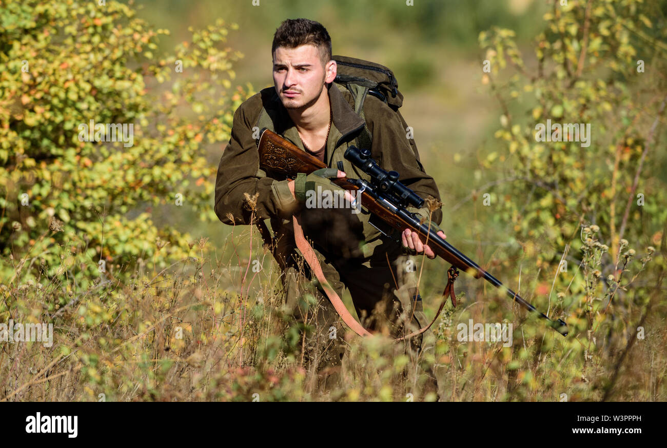 Hunting is brutal masculine hobby. Bearded serious hunter spend leisure hunting. Hunter hold rifle. Man wear camouflage clothes nature background. Hunting permit. Hunting equipment for professionals. - Stock Image