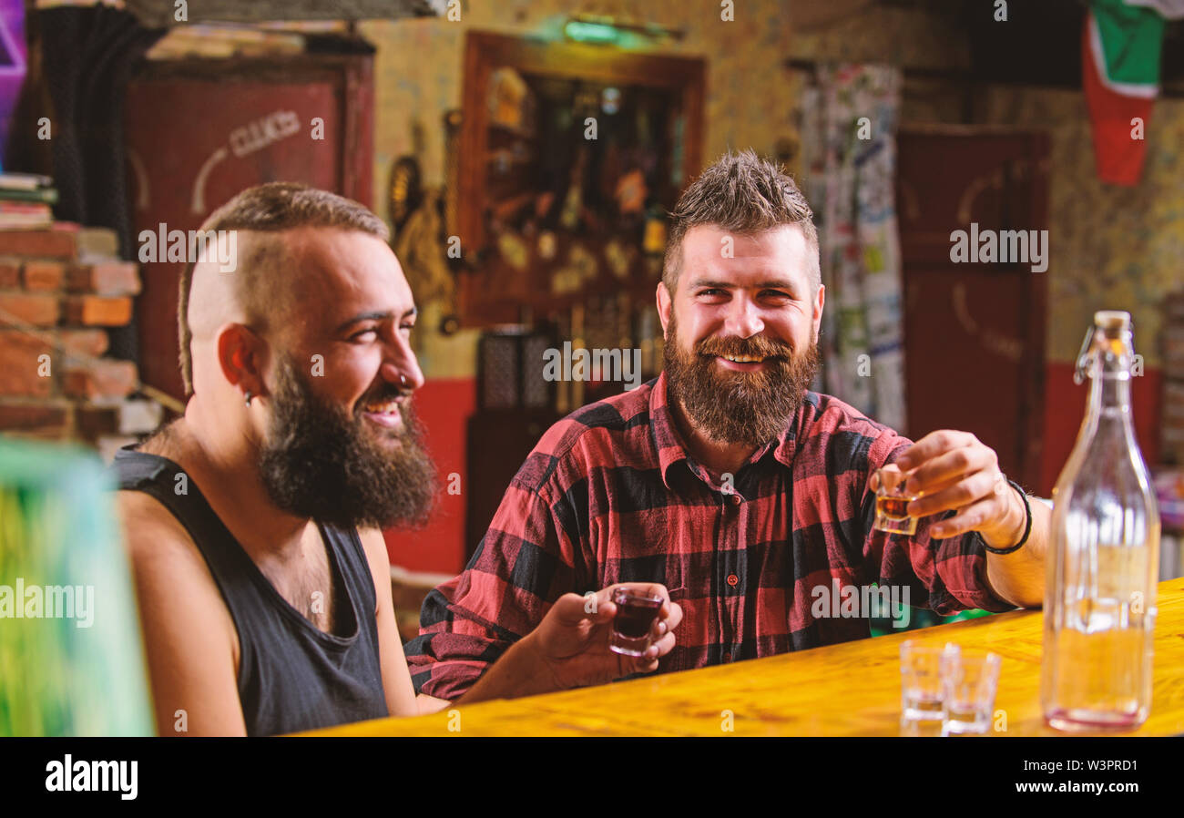 Men drunk relaxing at pub having fun. Strong alcohol drinks. Friends relaxing in pub. Men drinking alcohol together. Alcohol addiction. Hipster brutal - Stock Image