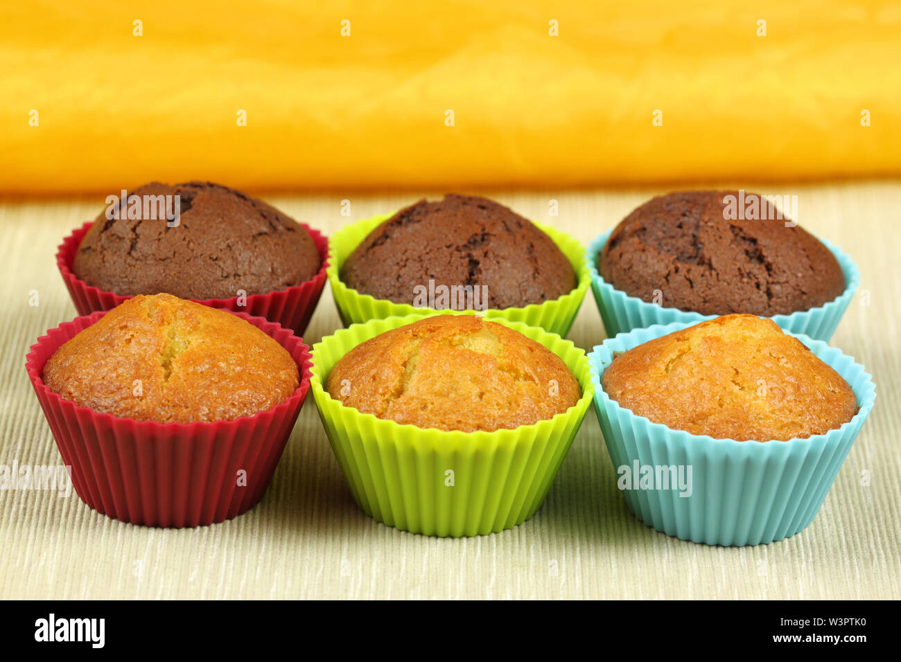 delicious cupcakes in colorful molds - black and white cakes - Stock Image