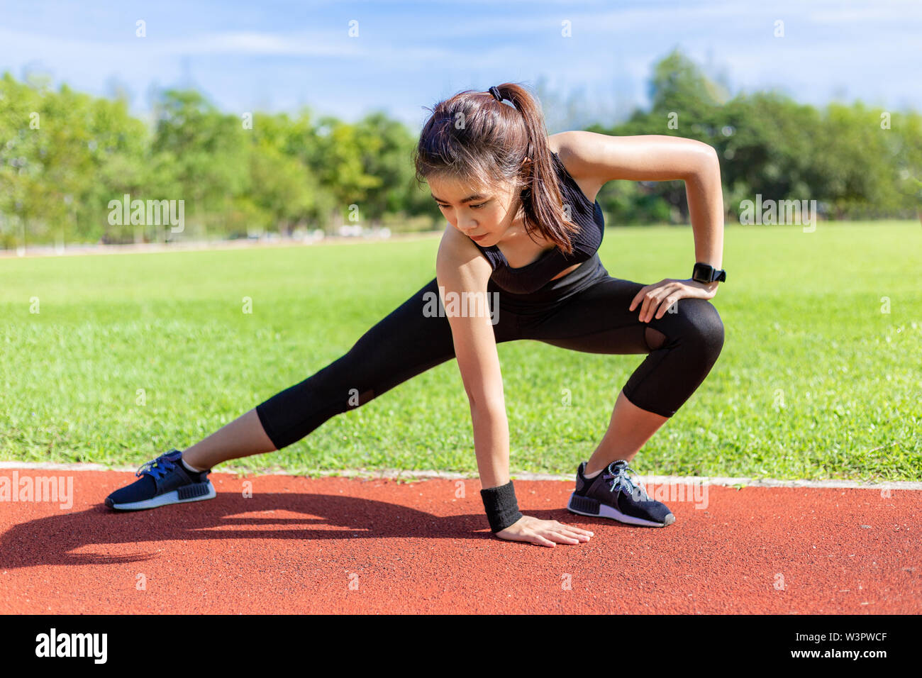 Beautiful young Asian woman stretching before exercising in the morning at a running track, healthy lifestyle - Stock Image