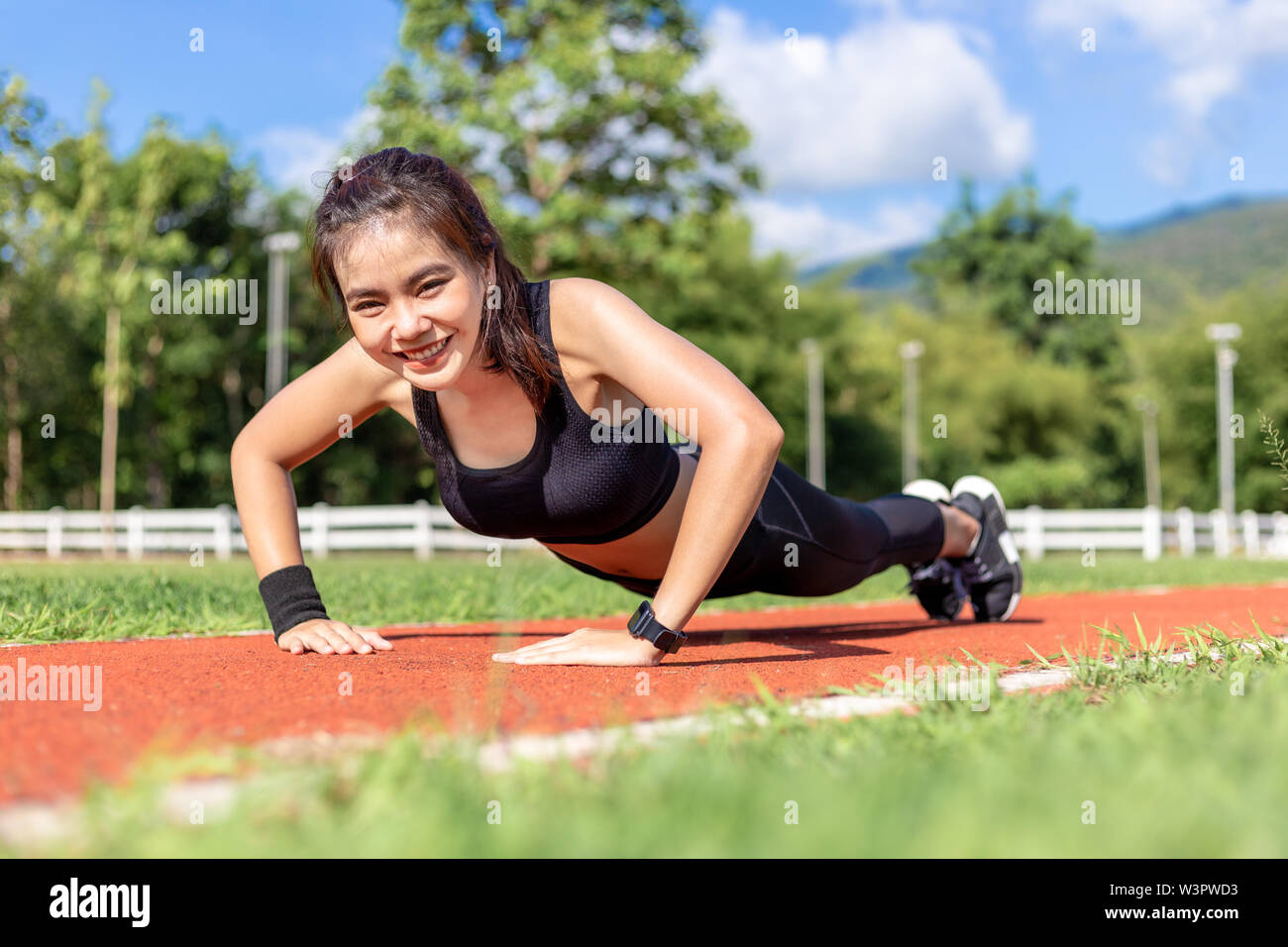 Happy beautiful young Asian woman doing push up exercise in the morning at a running track on a bright sunny day - Stock Image