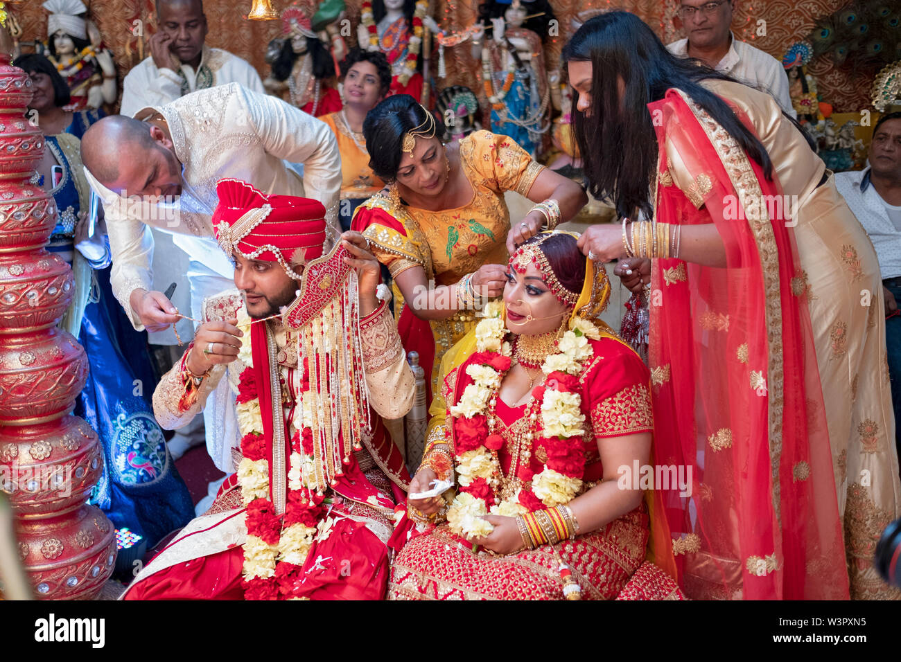 Near the conclusion of a traditional Hindu wedding, family members remove the face coverings from the bride & groom. In Queens, New York City. Stock Photo