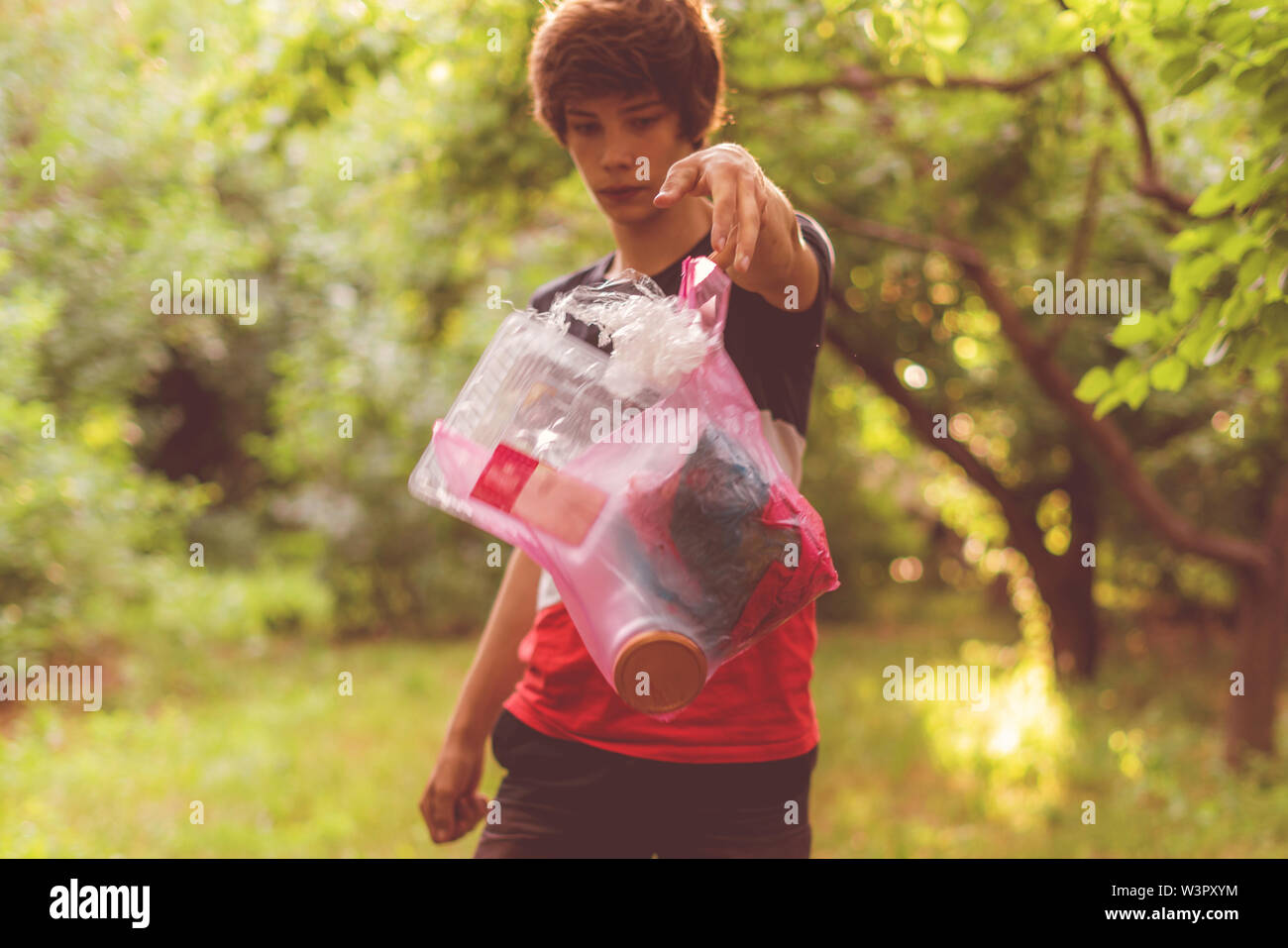 young person throw the plastic package with trash away in the nature park zone, environmental pollution - Stock Image