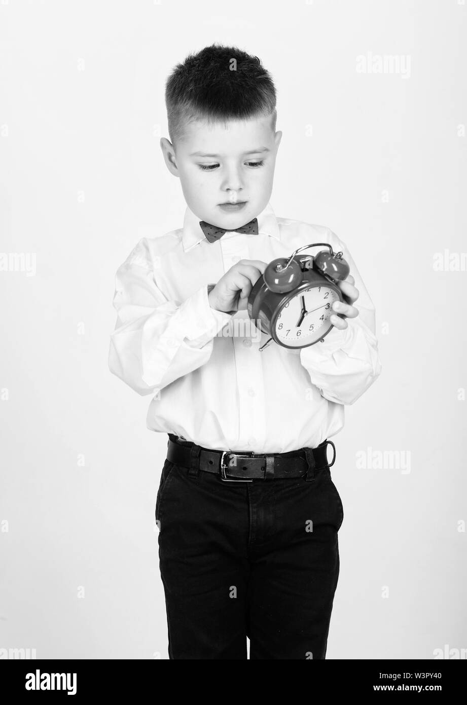 happy child with retro clock in bow tie. little boy with alarm clock. Time to relax. Party time. Businessman. Formal wear. Time management. Morning. tuxedo kid. Happy childhood. Memorable morning. - Stock Image