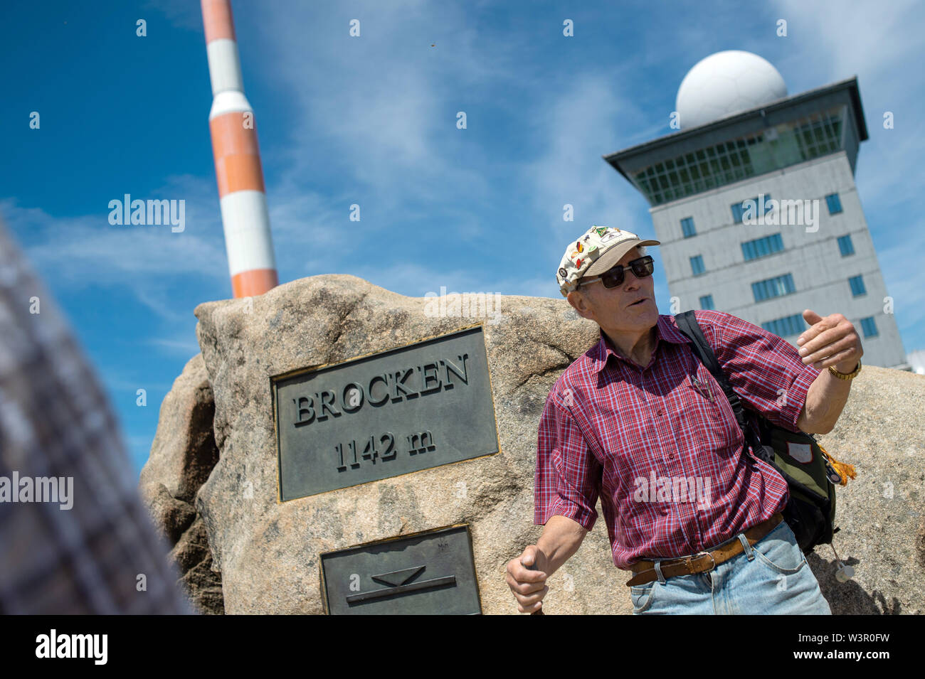 25 June 2019, Saxony-Anhalt, Wernigerode: The record hiker Benno Schmidt, who became famous as Brocken-Benno, stands on the Brocken. The summit of the Harz Mountains was opened to the public on 03 December 1989. Benno Schmidt is ambassador of the Green Belt, near which the Brocken lies. Before the fall of communism, the Brocken was a military restricted area. Photo: Klaus-Dietmar Gabbert/dpa-Zentralbild/ZB - Stock Image