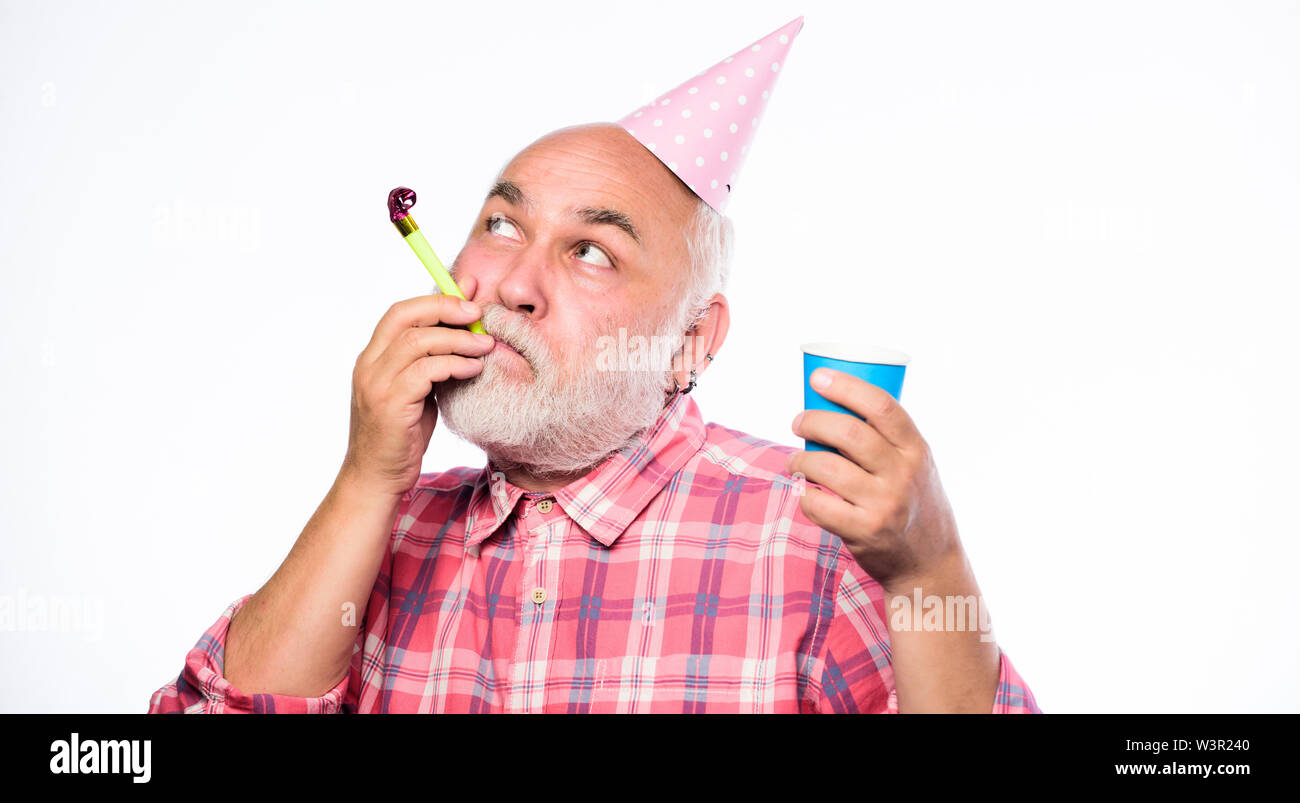 party time. happy birthday. corporate party. man hold party cone hat and whistle. happy man with beard. retirement party. anniversary holiday celebration. mature bearded man in pionted hat. - Stock Image