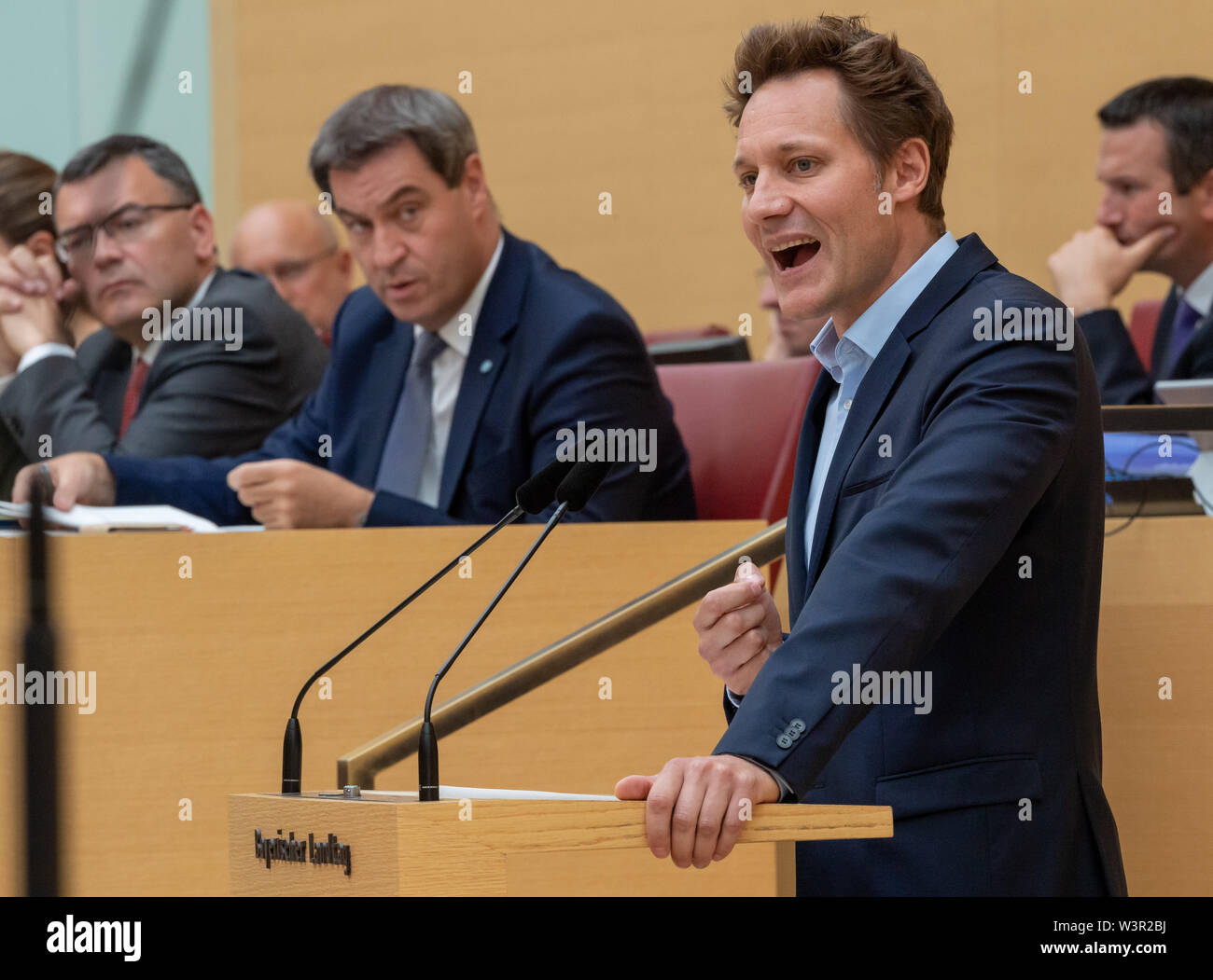 Munich, Germany. 17th July, 2019. Ludwig Hartmann, leader of the parliamentary group Bündnis 90/Die Grünen in the Bavarian parliament, will speak during the session of the Bavarian parliament. Behind him sits Markus Söder (CSU), Prime Minister of Bavaria. The main topics are the adoption of the legislative package for more environmental and species protection, including the draft law of the petition for a referendum 'Save the bees'. Credit: Peter Kneffel/dpa/Alamy Live News - Stock Image