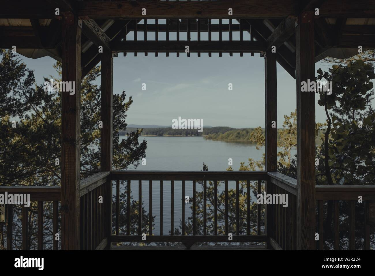 The beautiful view of the lake with a shoreline from a wooden arbor - Stock Image