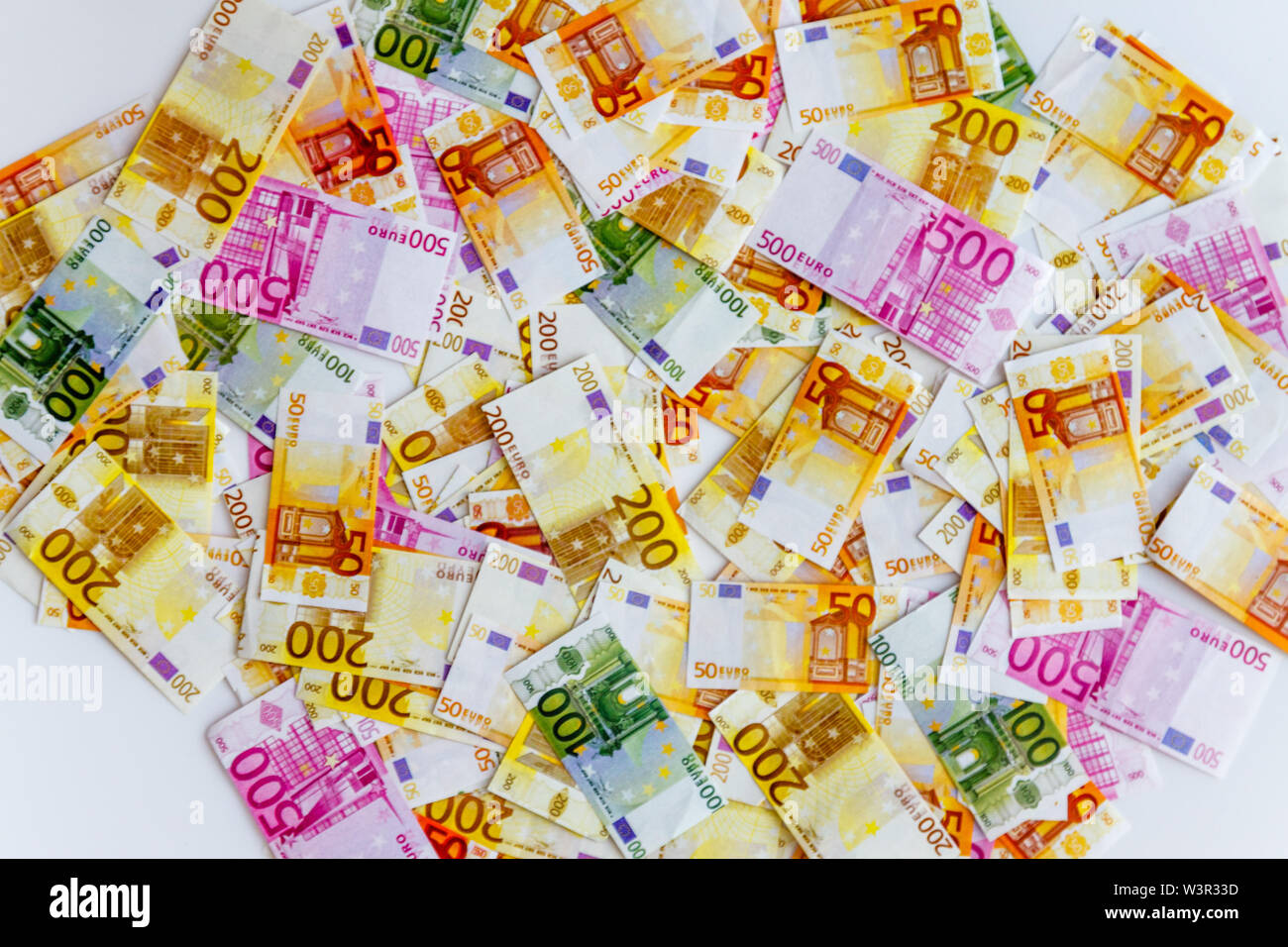 a lot of euro banknotes on a white background and a magnifying glass on top, top view. - Stock Image
