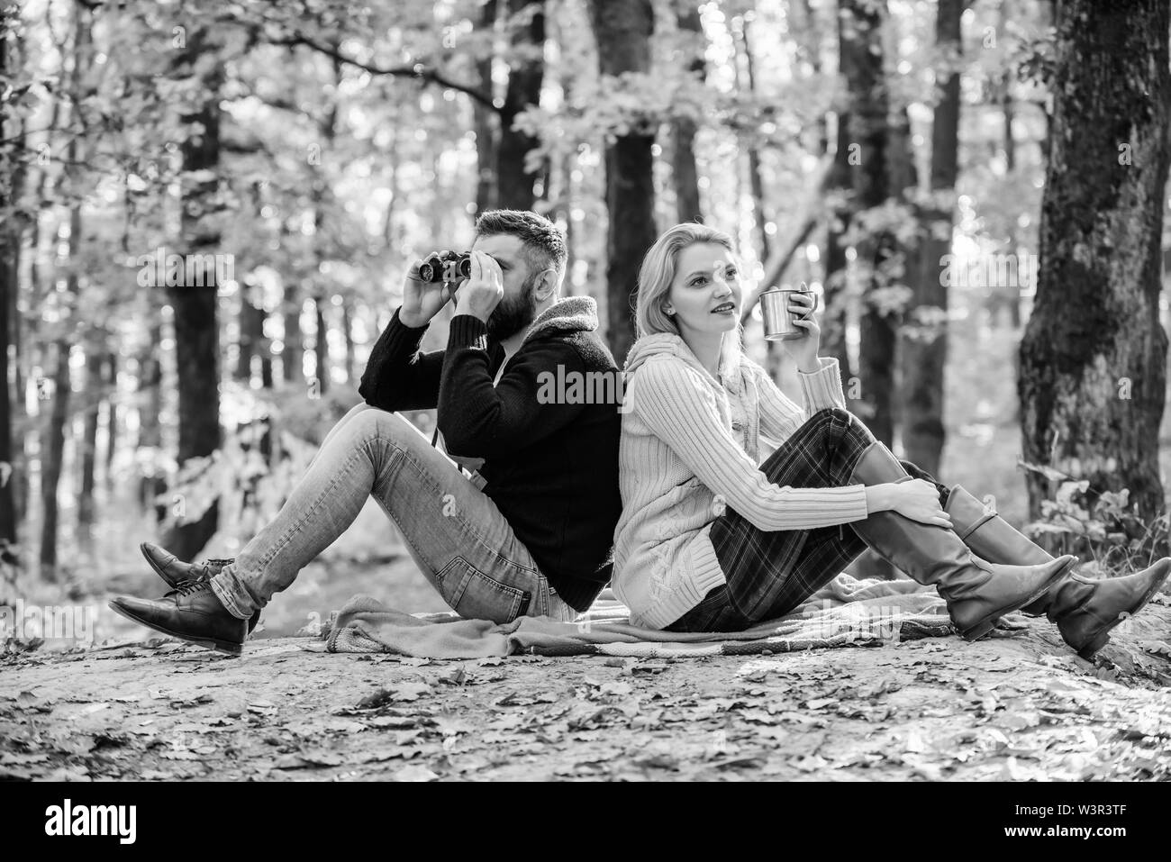 Relaxing in park together. Happy loving couple relaxing in park together. Couple in love tourists relaxing picnic blanket. Man with binoculars and wom - Stock Image