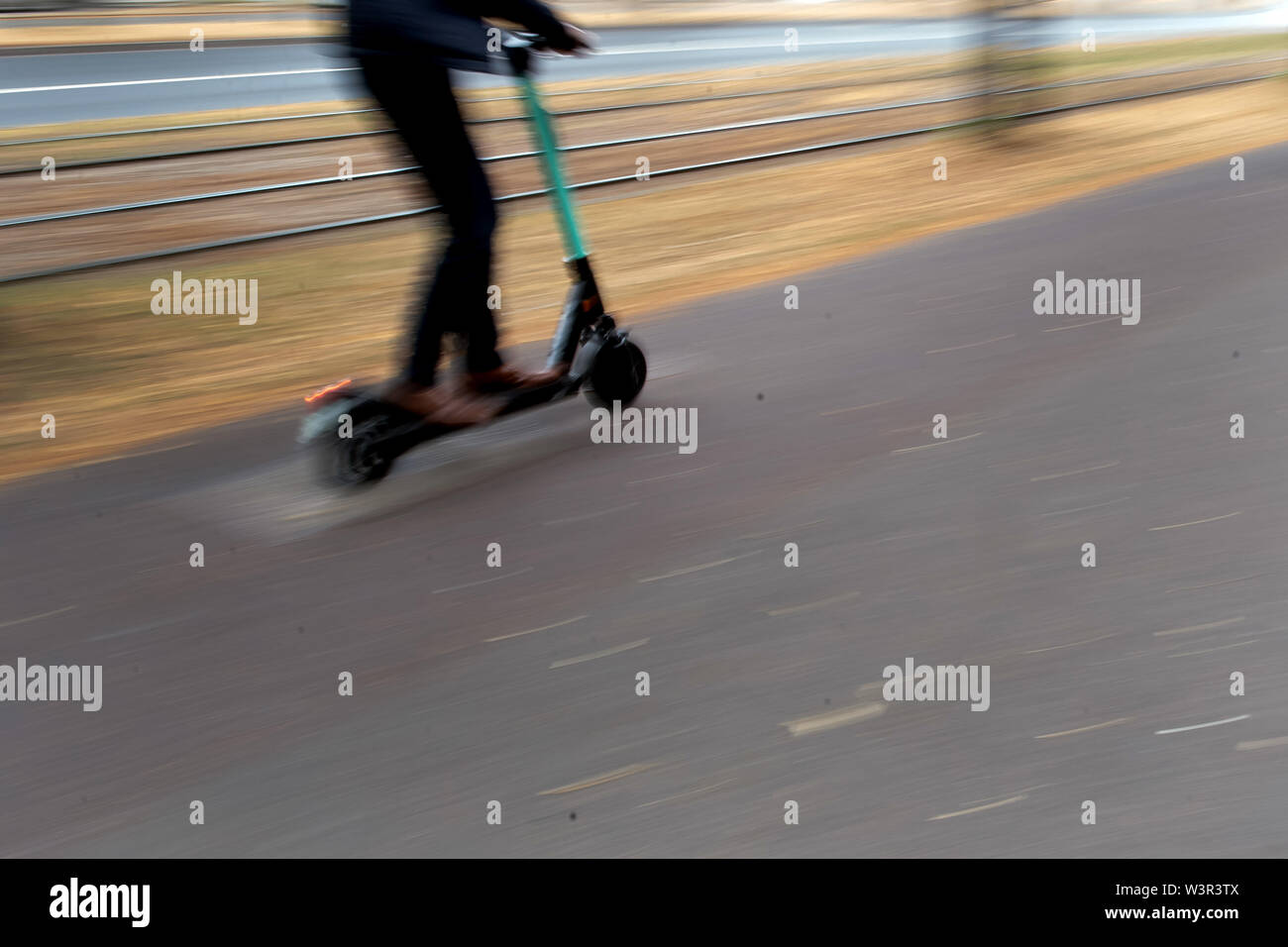 Duesseldorf, Germany. 17th July, 2019. A man drives an electric pedal scooter through the city on a cycle path separated from the sidewalk next to tram tracks. In view of increasing reports of accidents with electric scooters and of drunken drivers, Federal Transport Minister Andreas Scheuer is calling for tougher action. Credit: Federico Gambarini/dpa/Alamy Live News - Stock Image