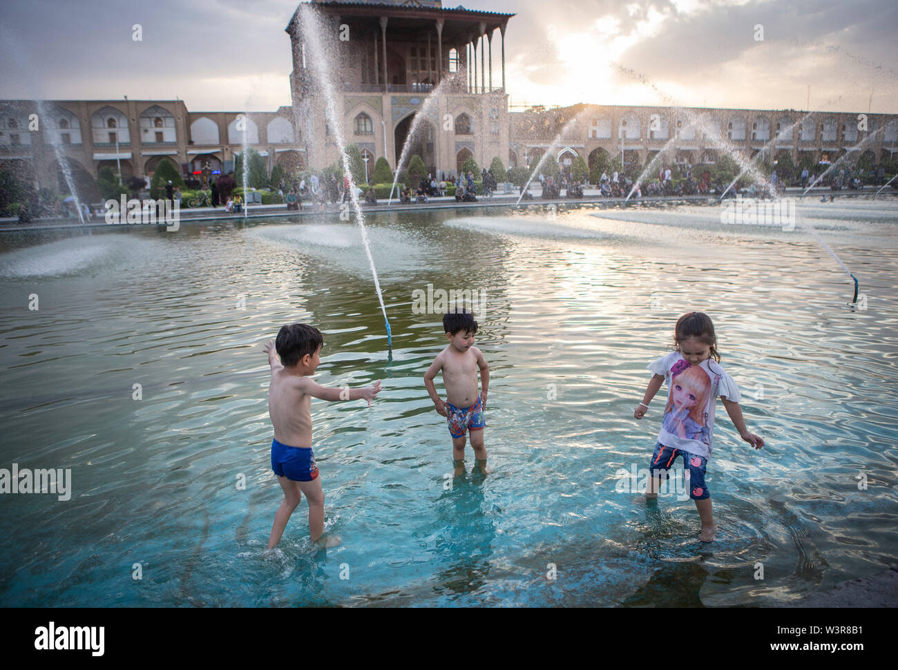 Isfahan, Iran. 16th July, 2019. Children cool themselves off in the water on a hot day in Isfahan, Iran, July 16, 2019. Credit: Ahmad Halabisaz/Xinhua/Alamy Live News - Stock Image