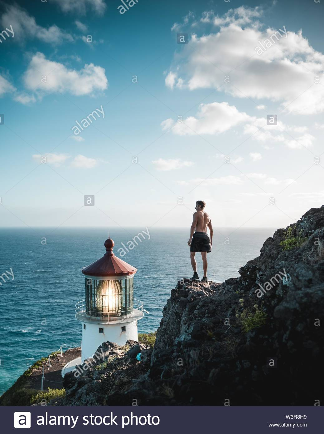 A shirtless fit male standing on a rocky cliff near a lighthouse beacon and the sea - Stock Image