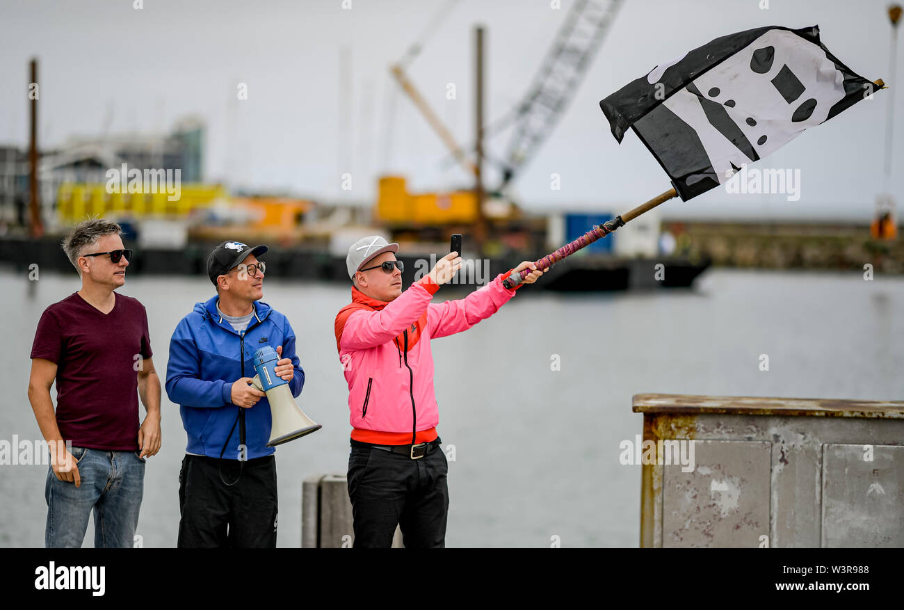 Helgoland, Germany. 17th July, 2019. The hip-hop band Fettes Brot, Martin Vandreier alias 'Doktor Renz' (l-r), Björn Warns alias 'Björn Beton' and Boris Lauterbach alias 'König Boris', waving a flag in front of the fans who came to the concert at Hafe'Helgoland. 700 visitors are expected in the sold out Nordseehalle. Credit: Axel Heimken/dpa/Alamy Live News - Stock Image