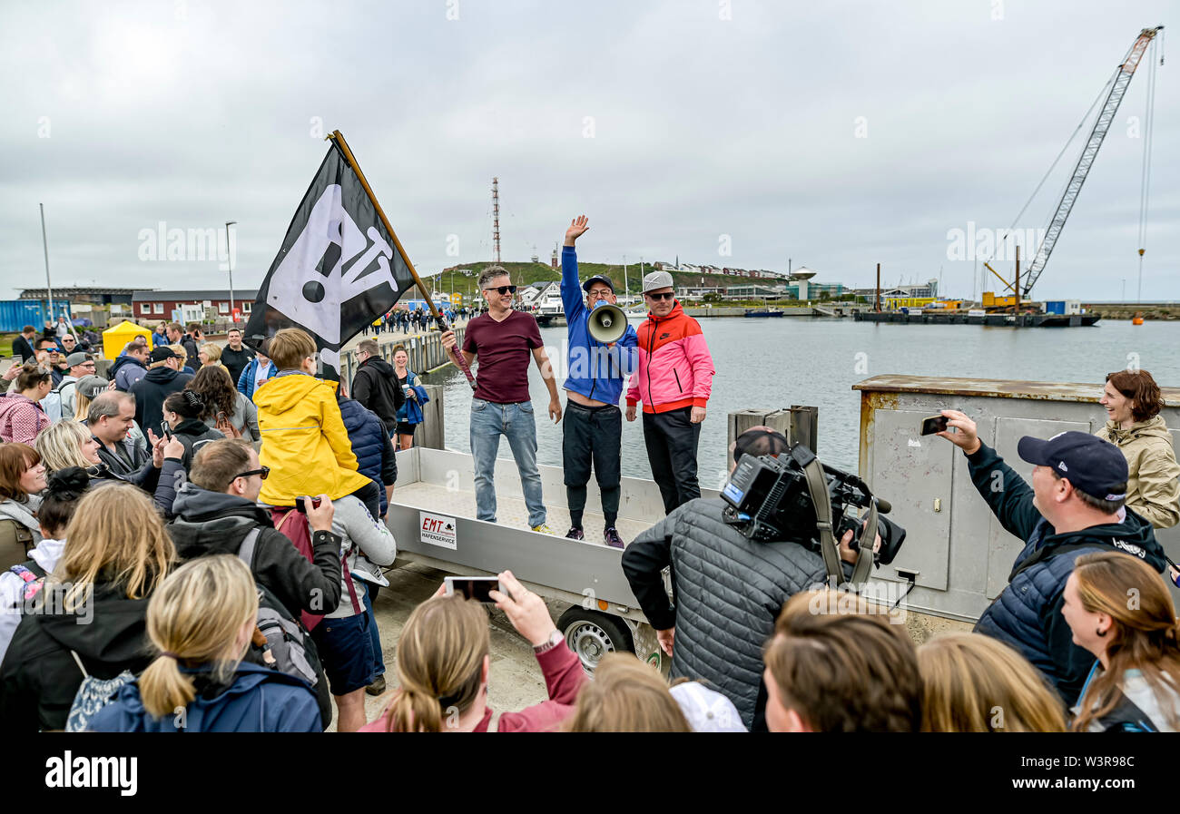Helgoland, Germany. 17th July, 2019. The hip-hop band Fettes Brot, Martin Vandreier alias 'Doktor Renz' (l-r), Björn Warns alias 'Björn Beton' and Boris Lauterbach alias 'König Boris', greets their fans at the harbour of Helgoland who came to the concert. 700 visitors are expected in the sold out Nordseehalle. Credit: Axel Heimken/dpa/Alamy Live News - Stock Image