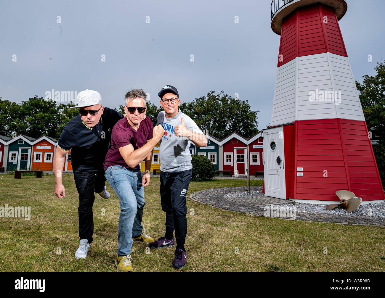 Helgoland, Germany. 17th July, 2019. The hip-hop band Fettes Brot, Boris Lauterbach alias 'König Boris' (l-r), Martin Vandreier alias 'Doktor Renz' and Björn Warns alias 'Björn Beton', are standing next to a Leuxchtturm on the island of Helgoland on the day of their concert. 700 visitors are expected in the sold out Nordseehalle. Credit: Axel Heimken/dpa/Alamy Live News - Stock Image