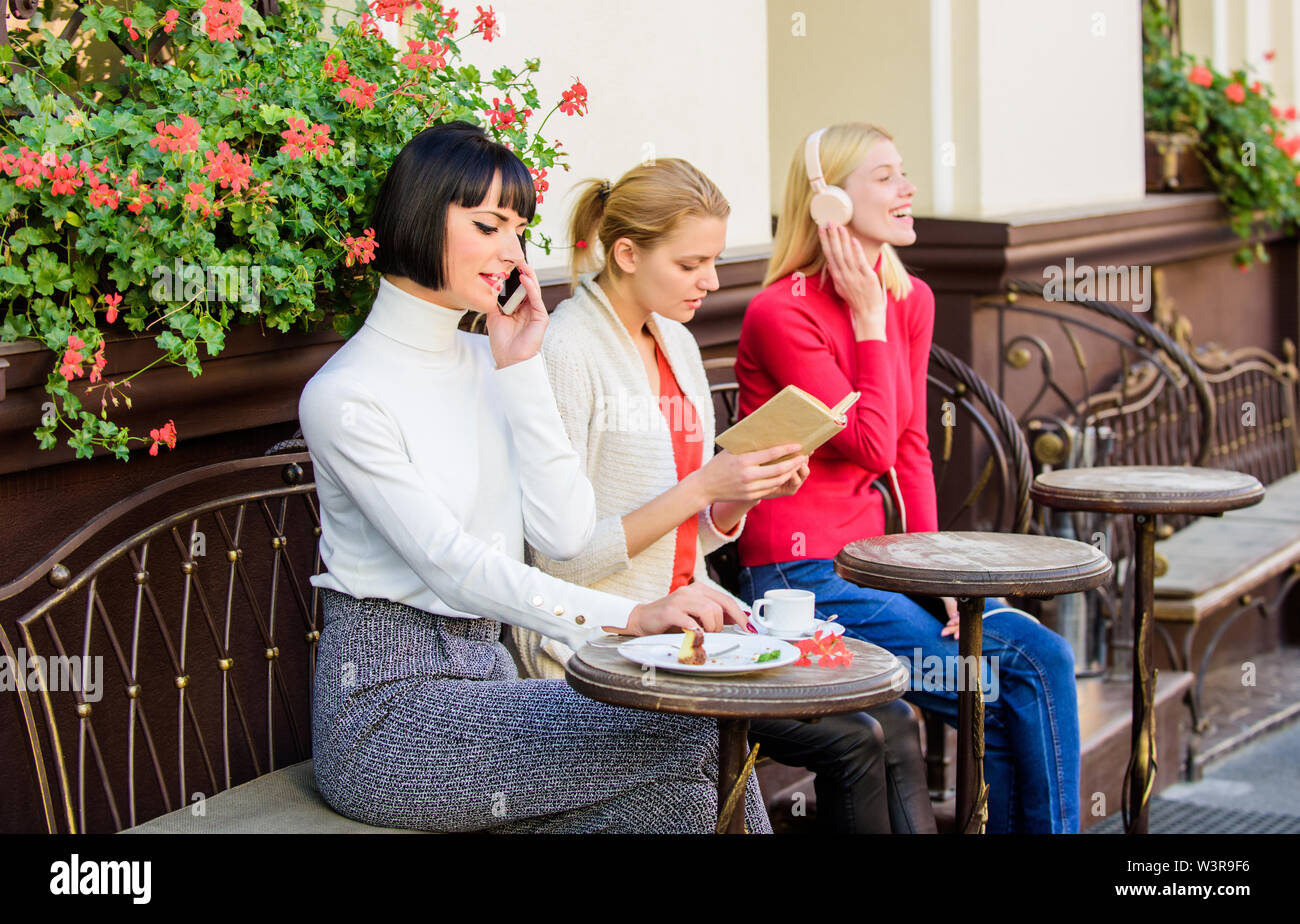 Female leisure. Weekend relax and leisure. Different interests. Hobby and leisure. Group pretty women cafe terrace entertain themselves with reading s - Stock Image