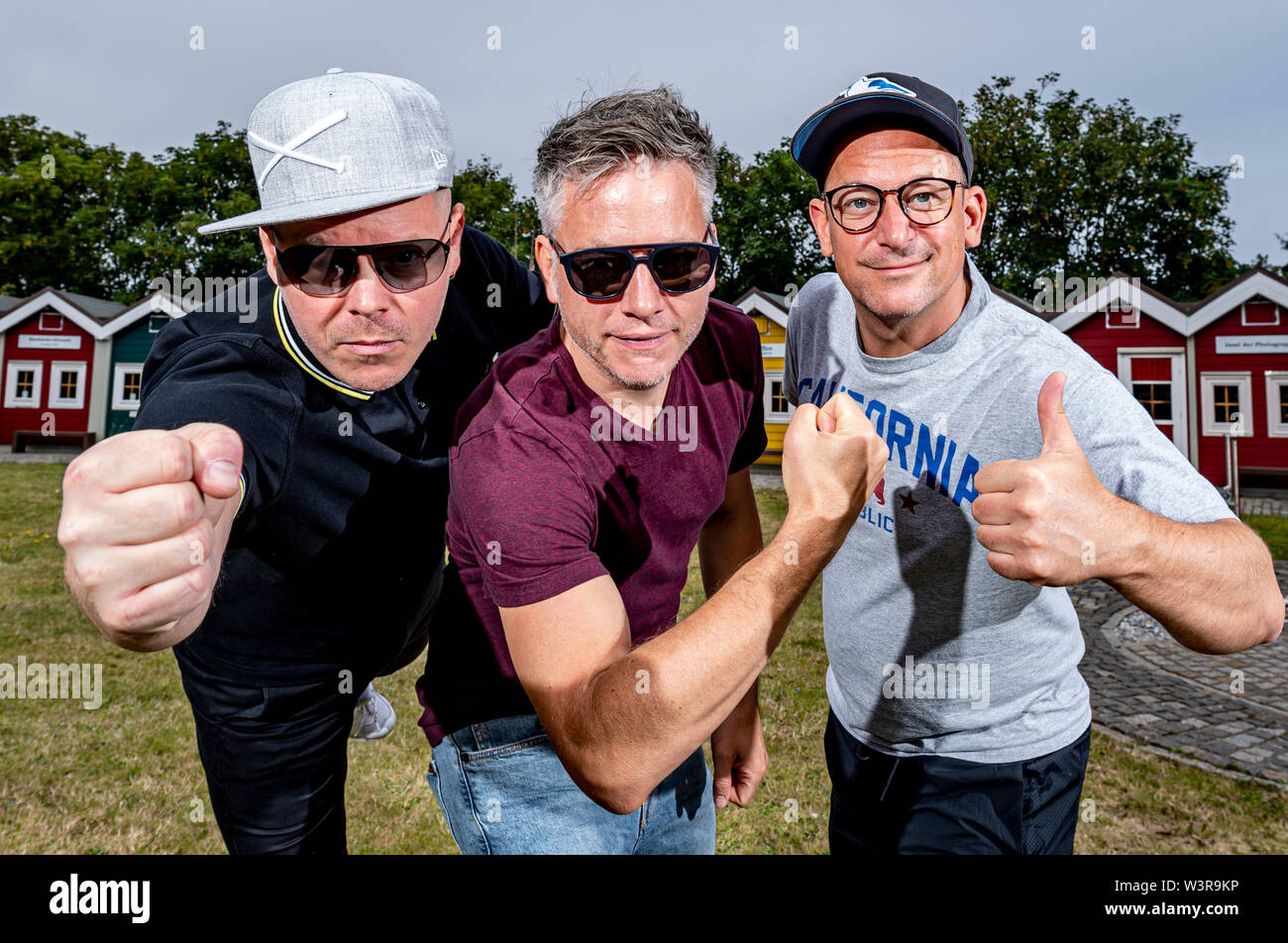 Helgoland, Germany. 17th July, 2019. The hip-hop band Fettes Brot, Boris Lauterbach alias 'König Boris' (l-r), Martin Vandreier alias 'Doktor Renz' and Björn Warns alias 'Björn Beton', are standing on a meadow on the island of Helgoland on the day of their concert. 700 visitors are expected in the sold out Nordseehalle. Credit: Axel Heimken/dpa/Alamy Live News - Stock Image