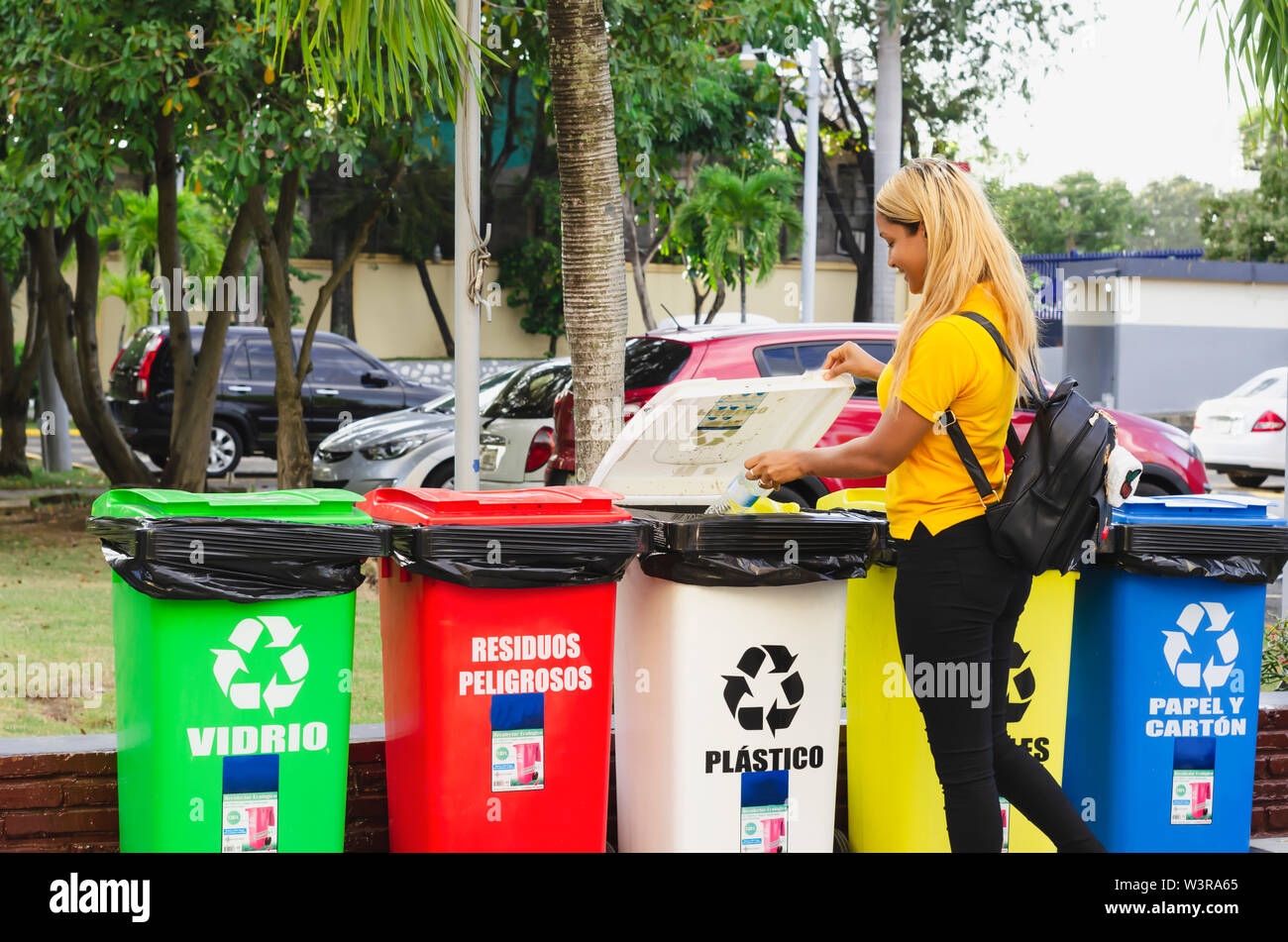 recycling of plastic bottles, girl of 20 to 25 years placing plastic bottle in deposits for processing - Stock Image