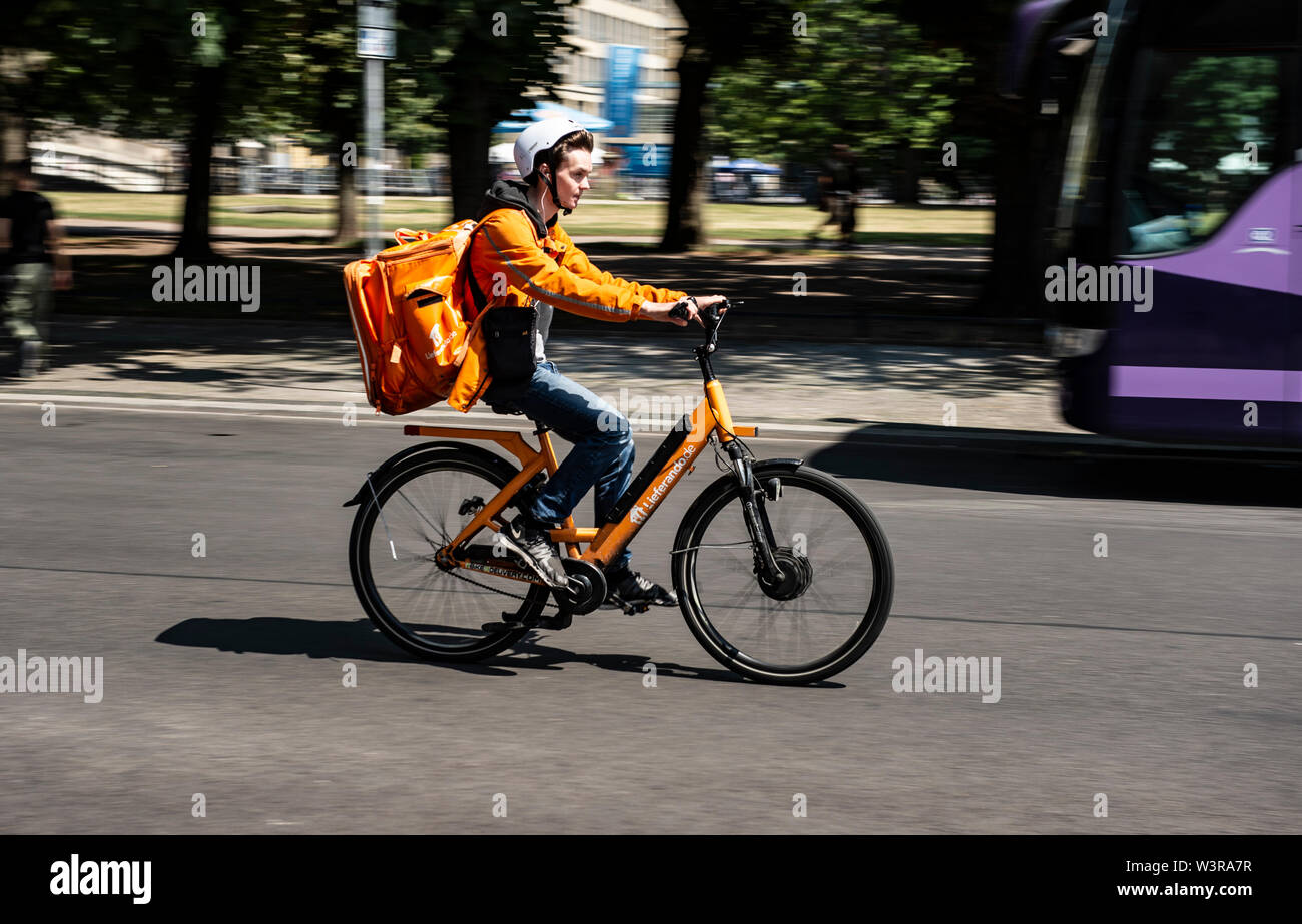 Berlin, Germany. 17th July, 2019. A driver of the delivery service Lieferando drives across a road. Credit: Paul Zinken/dpa/Alamy Live News - Stock Image