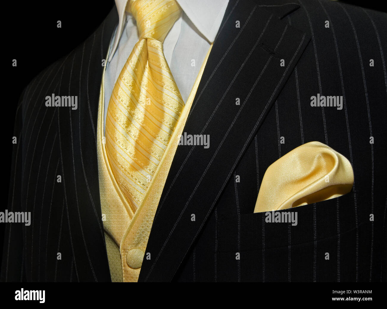 yellow tie and handkerchief accenting pinstriped tuxedo - Stock Image