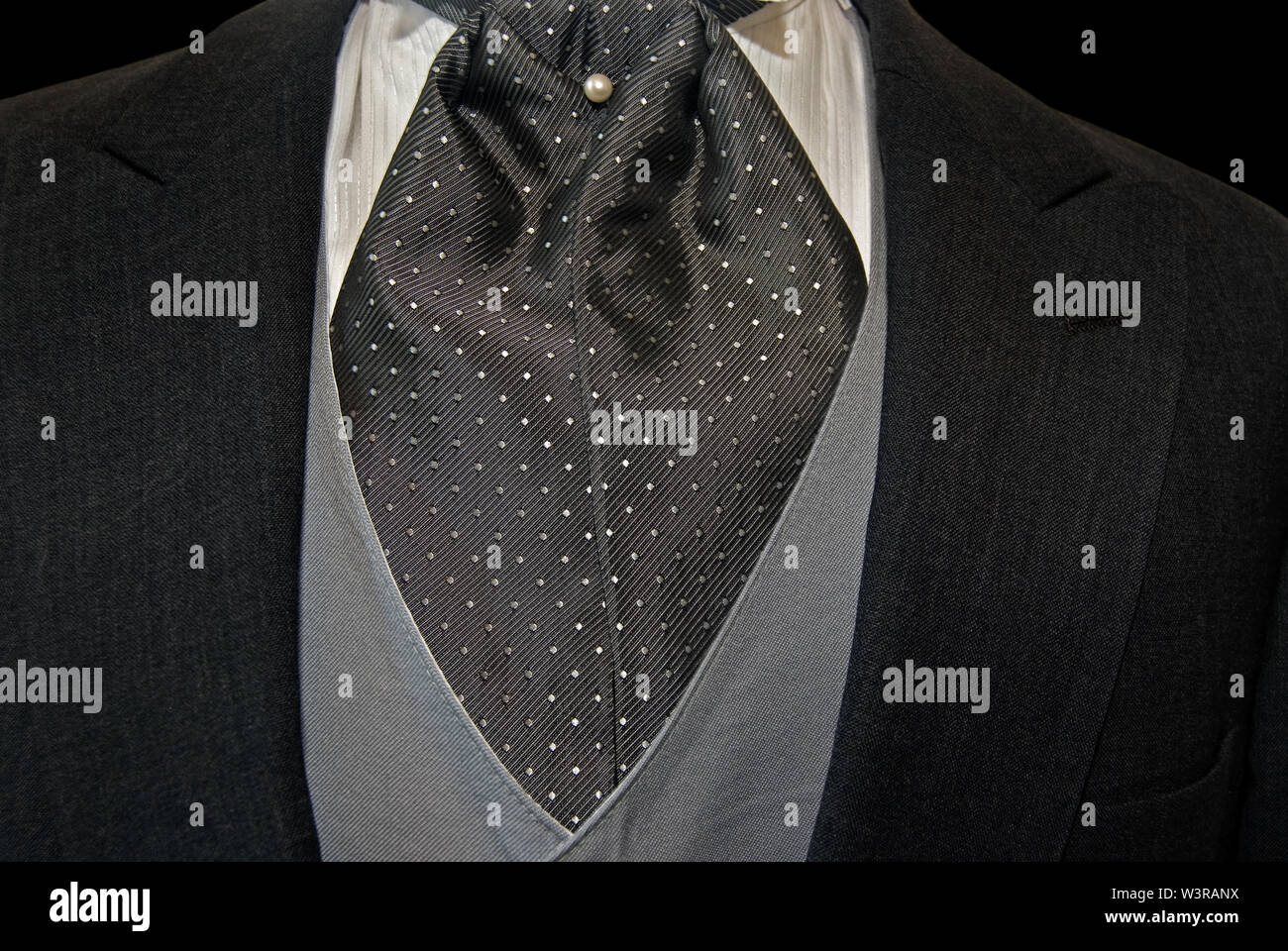 gray silk pin dot cravat with pearl stud accenting a tuxedo vest and jacket - Stock Image