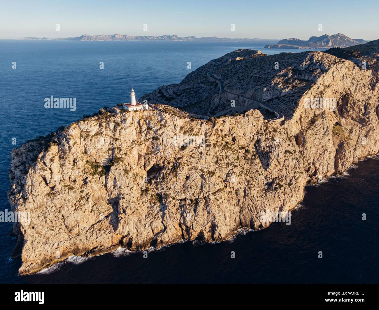 An aerial distant shot of a high rocky cliff with a white tower built on top in the middle of the ocean - Stock Image
