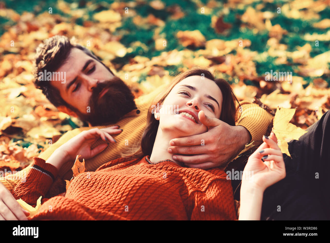 Man and woman with happy faces on grass and leaves background. Relationship and fall time concept. Girl and bearded guy or happy lovers on a date cudd - Stock Image