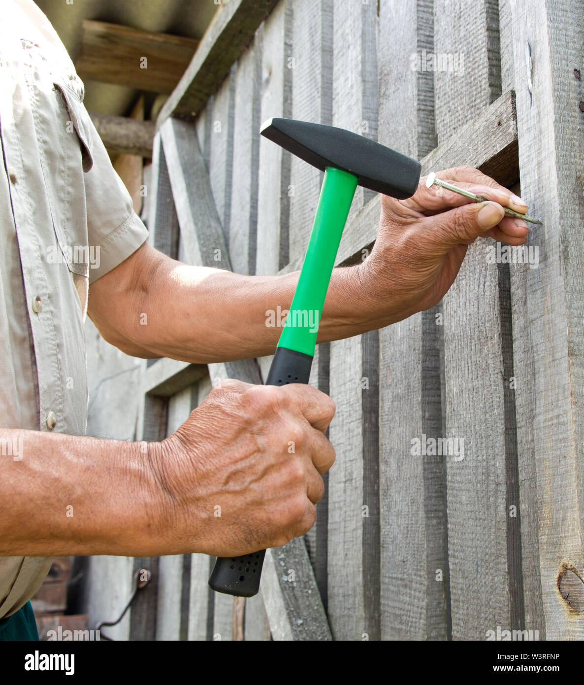To hammer a nail with a hammer. Older worker carpenter Stock Photo