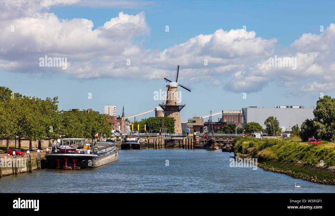Rotterdam, Netherlands. Traditional windmill and boats in river Maas at the harbor area. Stock Photo