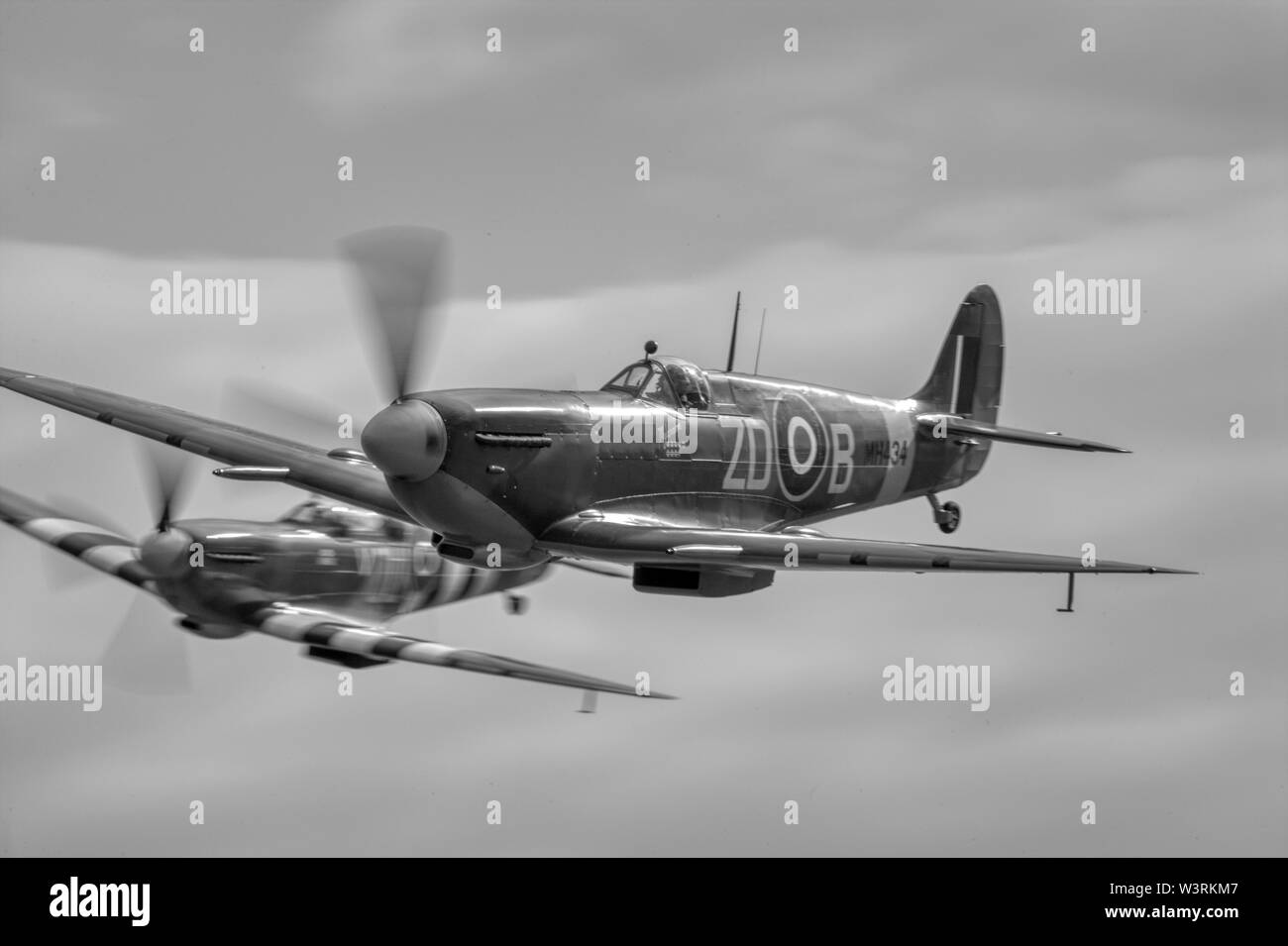 Vickers-Supermarine Spitfire LFIXb G-ASJV MH434/ZD-B world war 2 fighter aircraft in flight, panned with motion blur on the propeller blades. Stock Photo