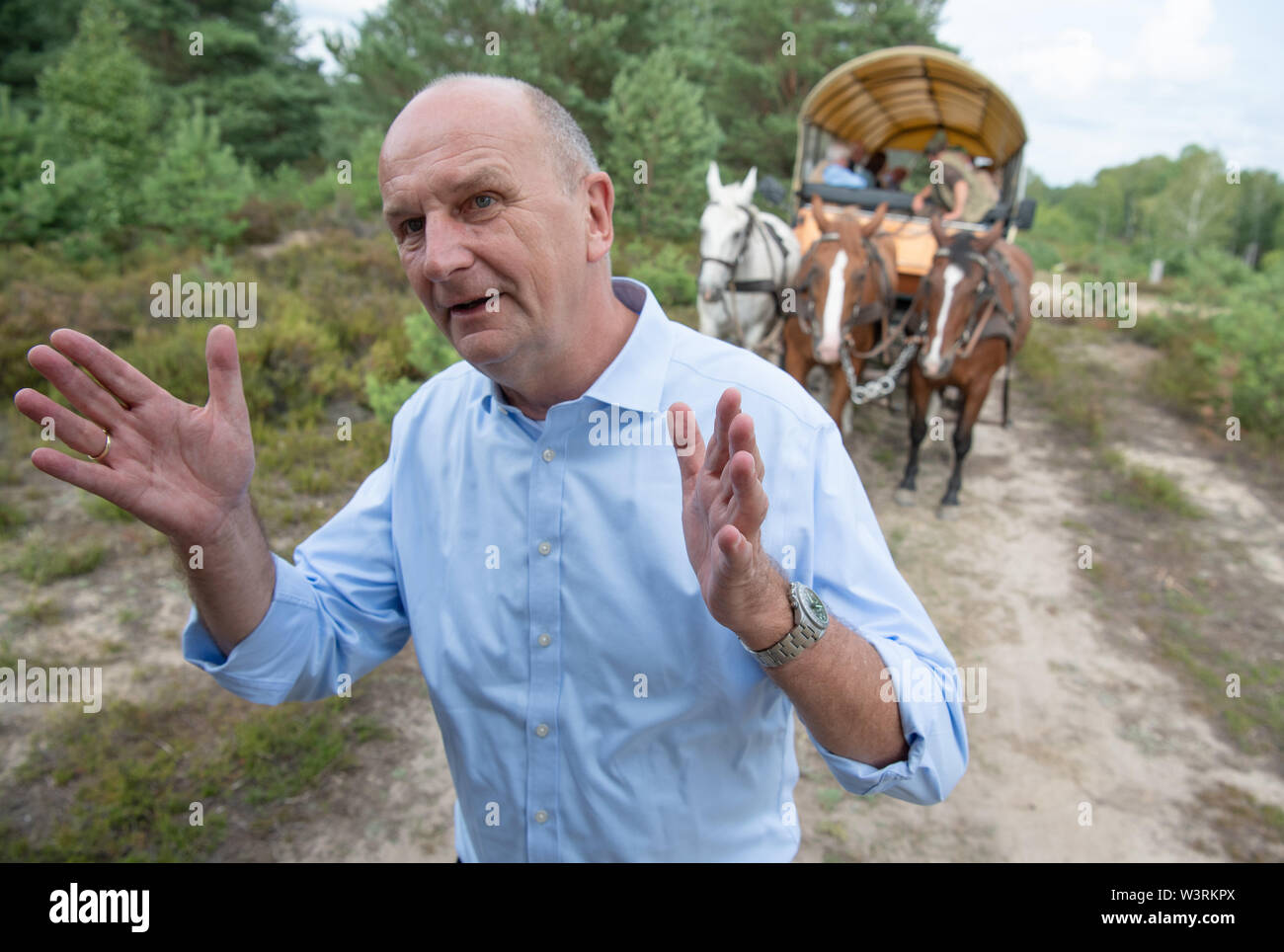 Pfalzheim, Germany. 17th July, 2019. Dietmar Woidke (SPD), Minister President of Brandenburg, speaks on the grounds of Sielmann's natural landscape Kyritz-Ruppiner Heide. There's a Kremser in the background. Credit: Soeren Stache/dpa/ZB/dpa/Alamy Live News - Stock Image