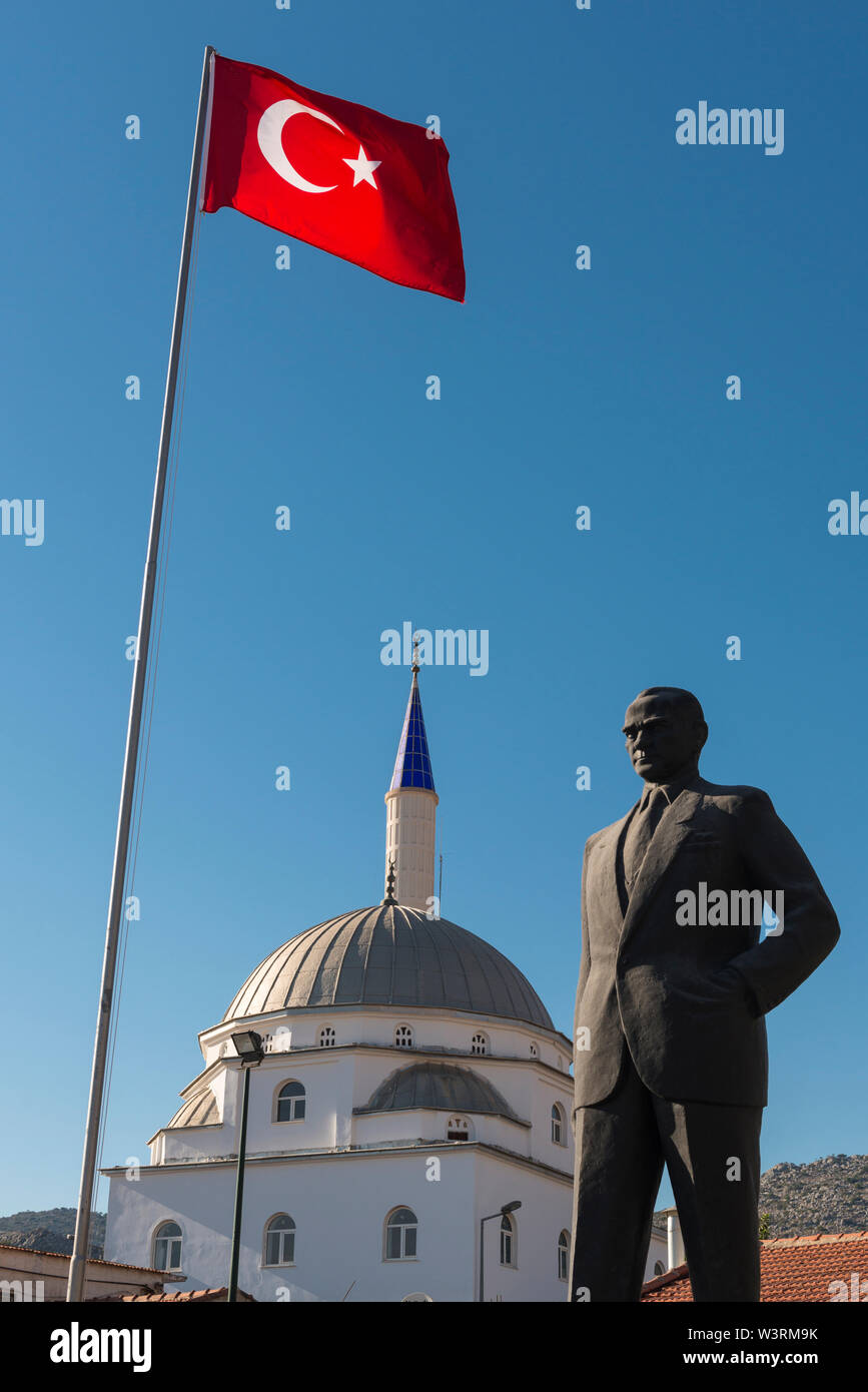 The Turkish flag flies above a statue of former President M. K. Ataturk, which stands beside a mosque in Bozburun, Turkey Stock Photo