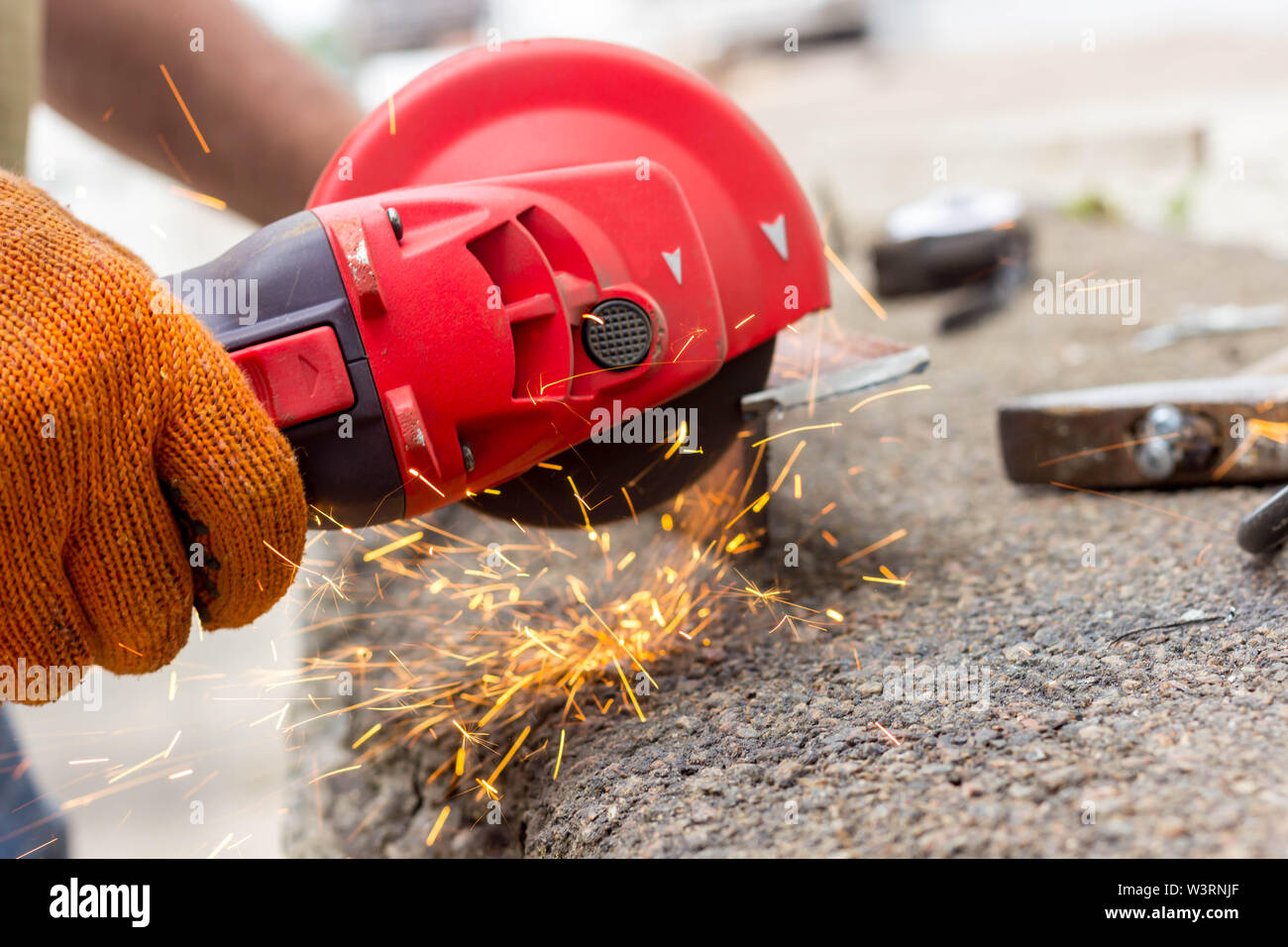 The worker uses an angle drive grinder to work with a metal corner. Angle drive grinder in action. - Stock Image