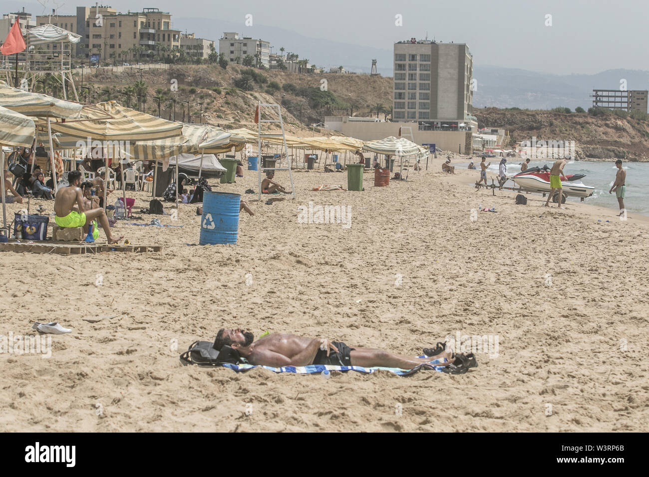Beirut, Lebanon. 17th July, 2019. A man sunbathes at the beach in Beirut during a sweltering day as temperatures exceed 40 degrees Celsius. Credit: Amer Ghazzal/SOPA Images/ZUMA Wire/Alamy Live News - Stock Image