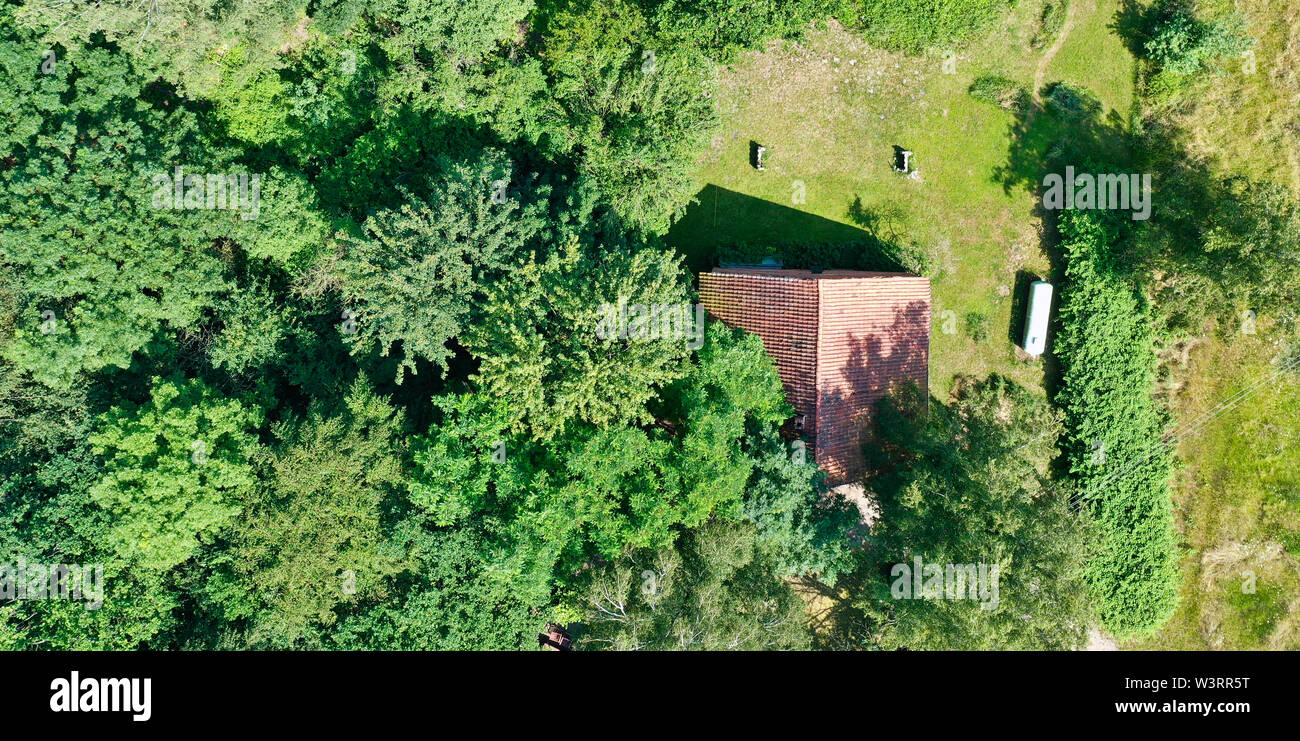 Aerial view from a vertical perspective of a small shed at the edge of a forest with a meadow in front of it. Stock Photo