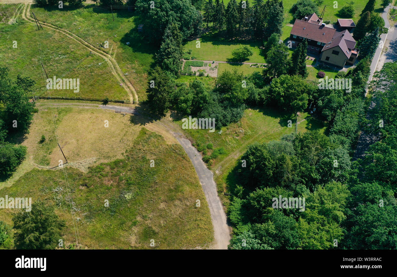 Aerial view of a meadow area with a few houses and a loose stock of bushes and trees. - Stock Image