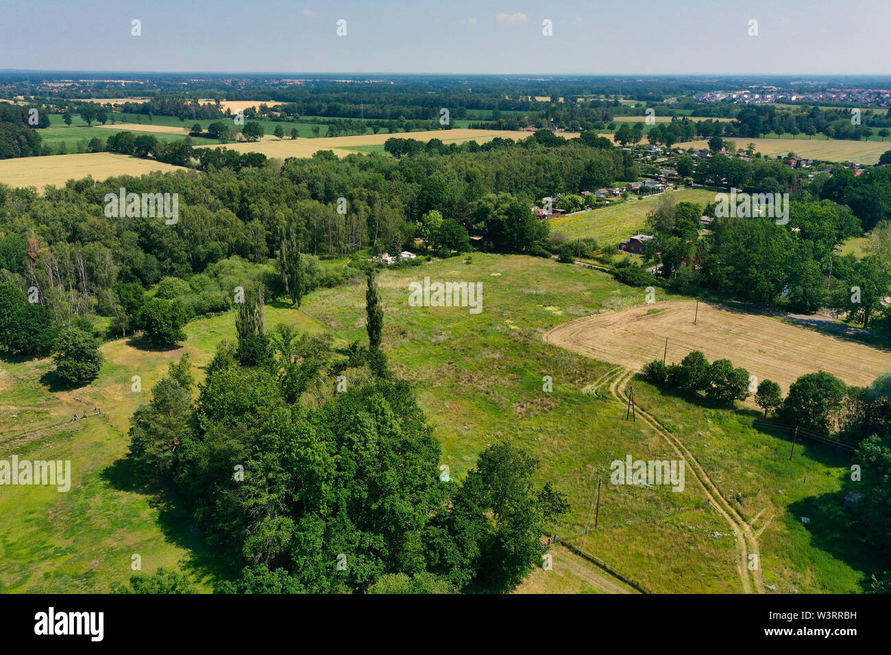 Aerial view of a meadow area with a few houses and a loose stock of bushes and trees. Stock Photo