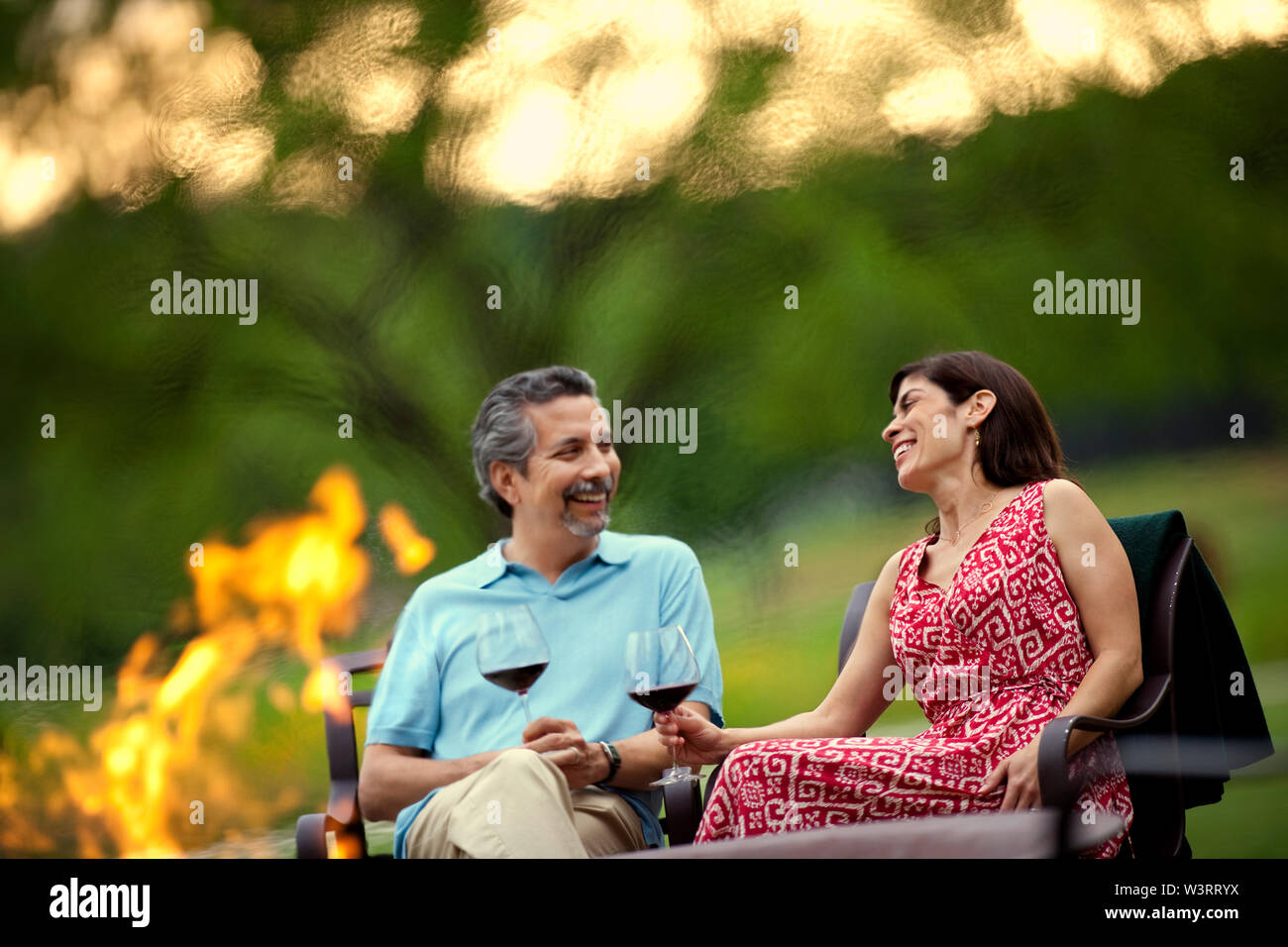 Smiling middle-aged couple relax with a glass of red wine beside a campfire in their garden in the late afternoon. Stock Photo