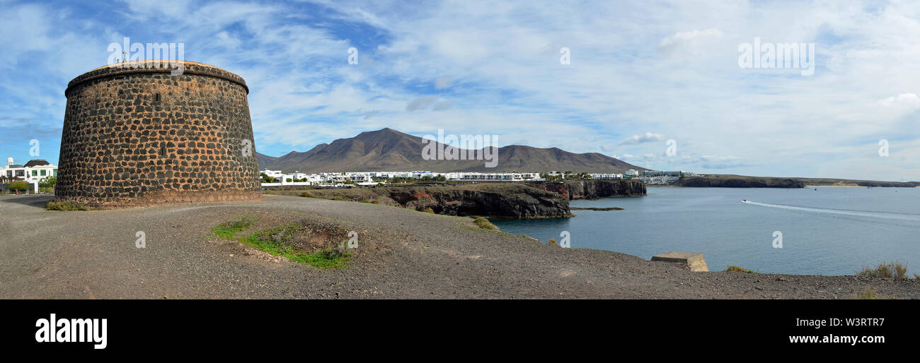Seafront Panorama of Playa Blanca Lanzarote with Old Napolionic Fort. - Stock Image