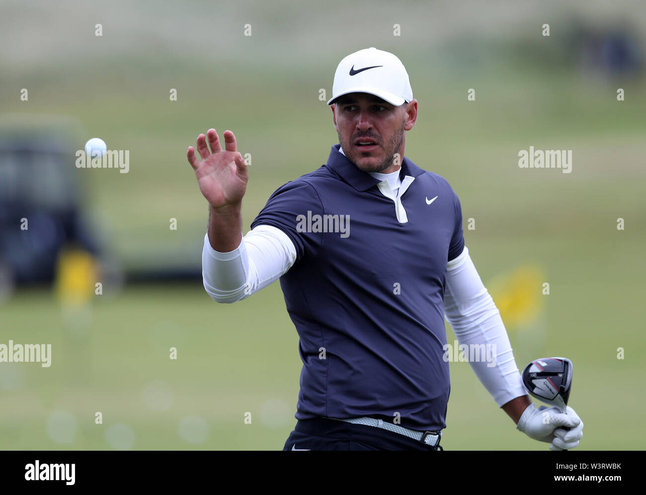 Portrush, Country Antrim, Northern Ireland. 17th July, 2019. The 148th Open Golf Championship, Royal Portrush Golf Club, Practice day; Brooks Koepka (USA) catches a ball tossed to him by his caddie on the practice range Credit: Action Plus Sports Images/Alamy Live News Stock Photo