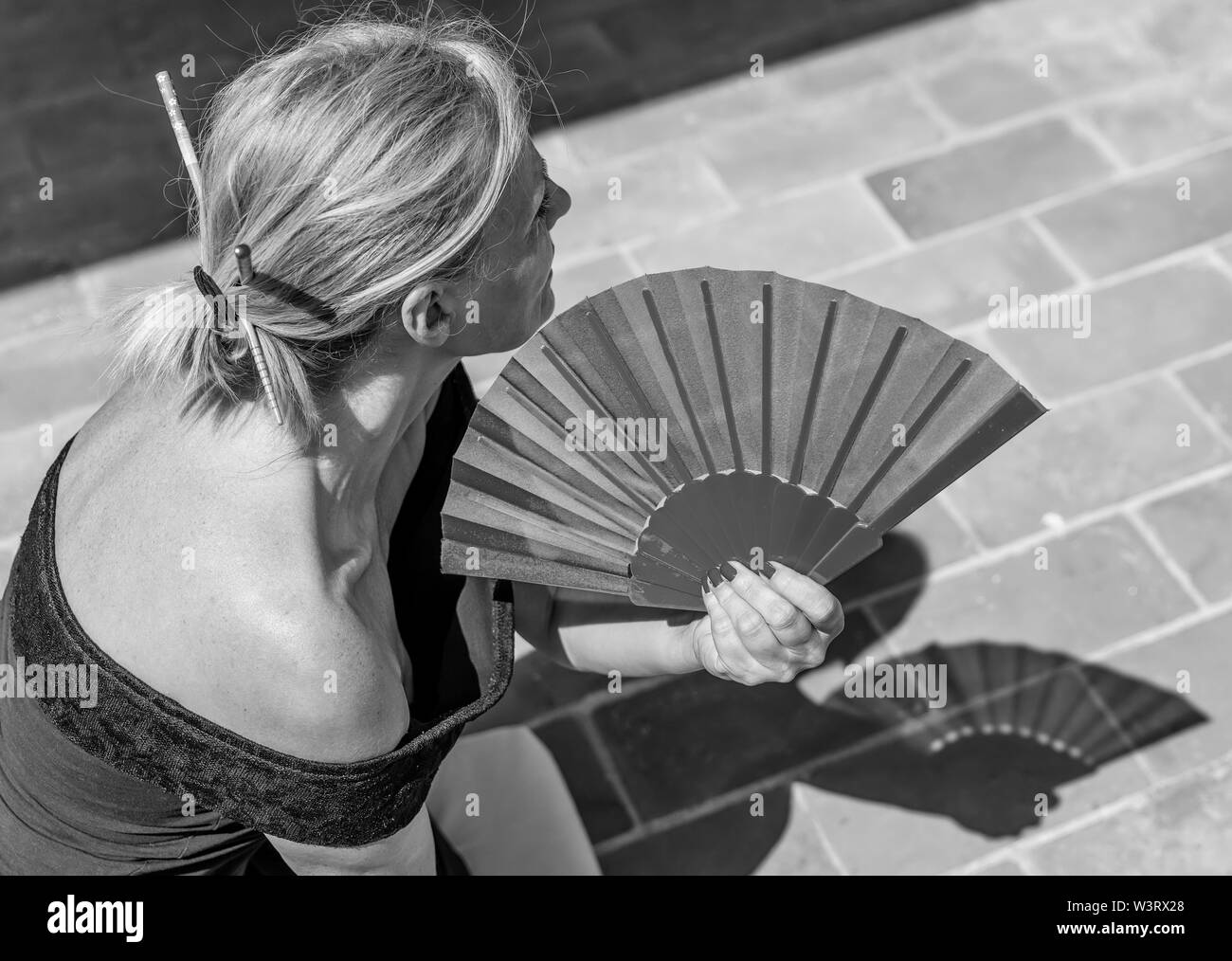 Beautiful caucasian woman uses a hand fan to cool off on a hot summer day - Stock Image