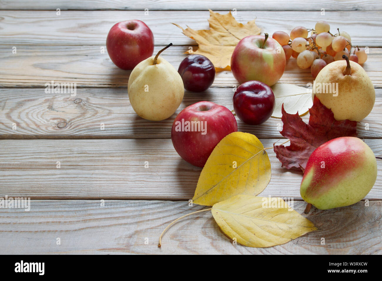 Autumn still life with various fruits are lying on a wooden desk. Autumn maple and other leaves. Harvesting. - Stock Image