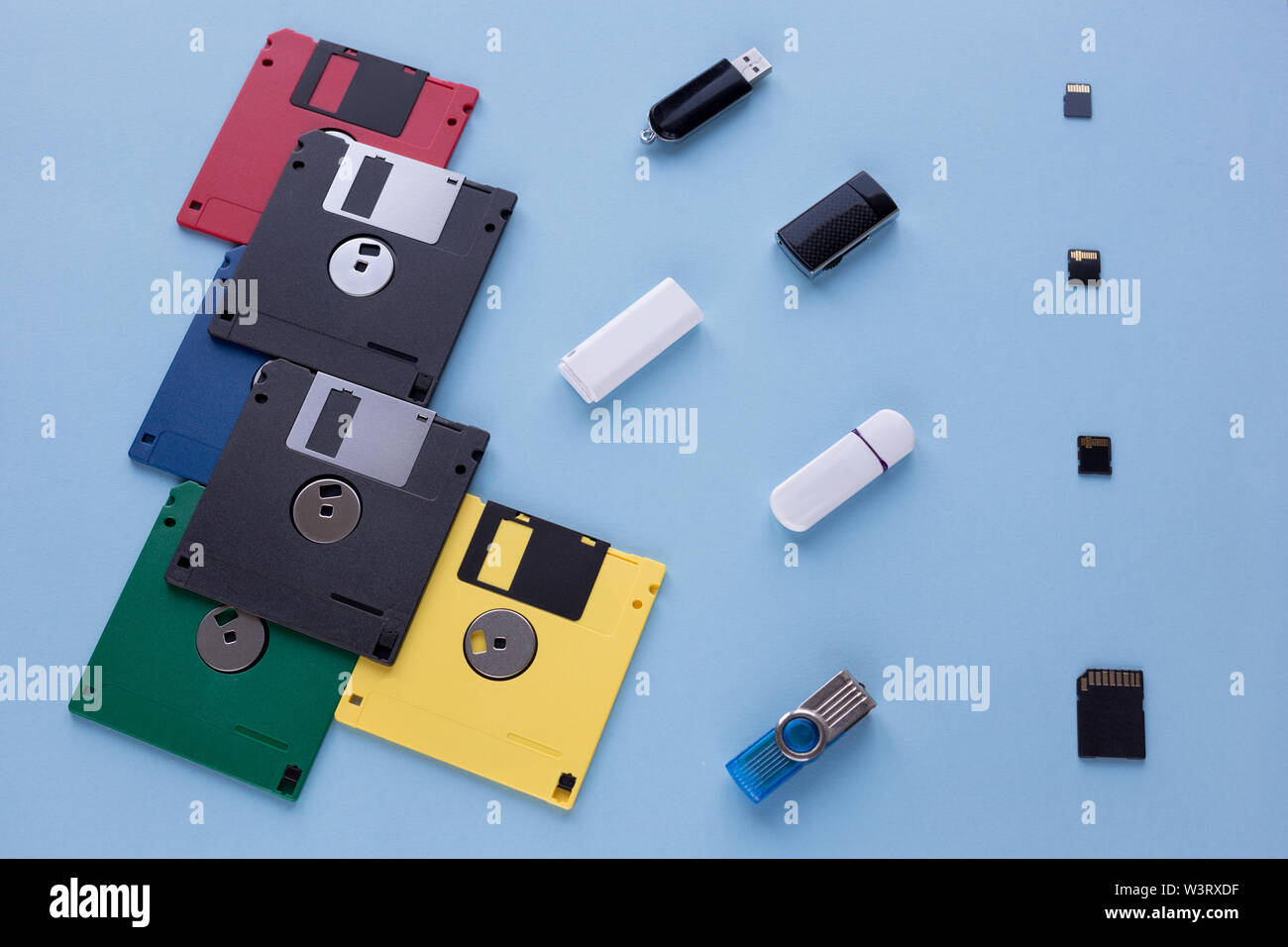 The evolution of digital data storage device. Floppy disks, flash drives and small memory cards. Isolated on a blue background. - Stock Image