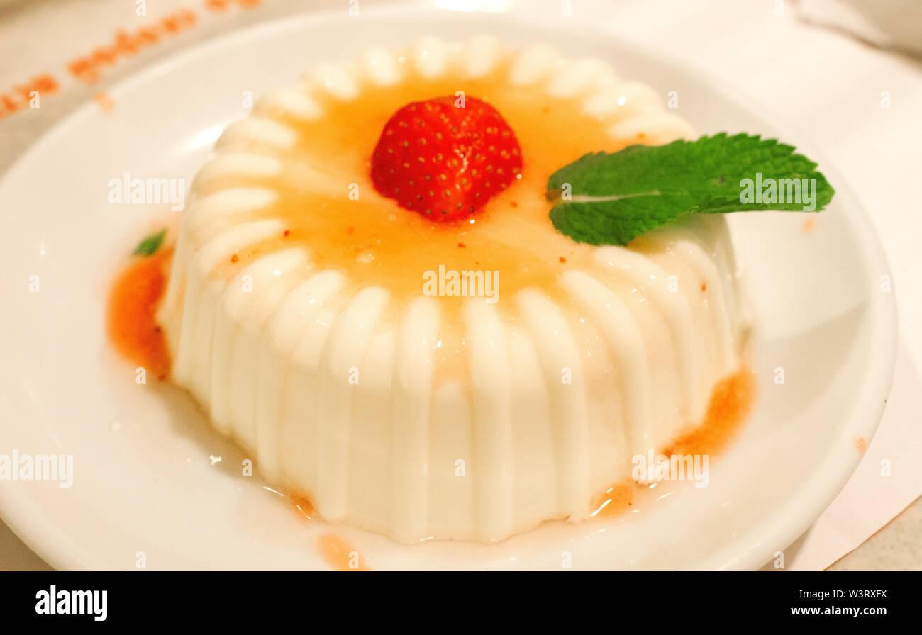 Italian panakota dessert on a plate with strawberries - Stock Image