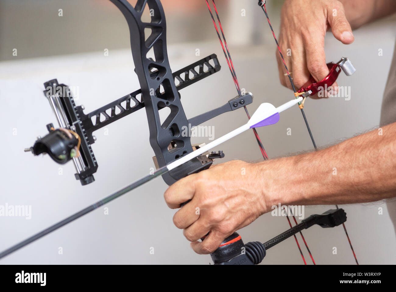 Archer hands close up, preparing the arrow for the shot . - Stock Image