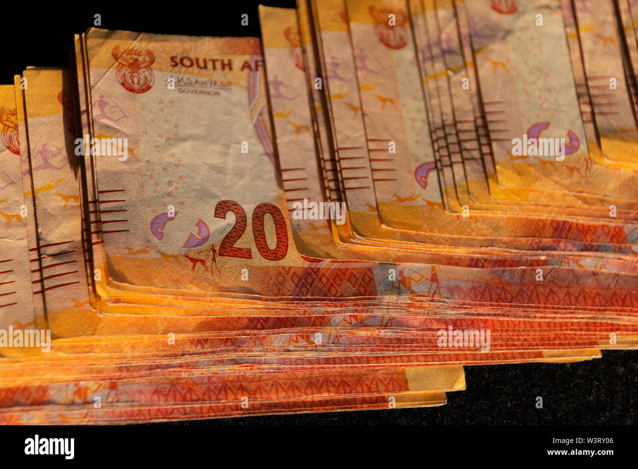 A close up view of two hundred south african notes in a pile on a isolated black background - Stock Image