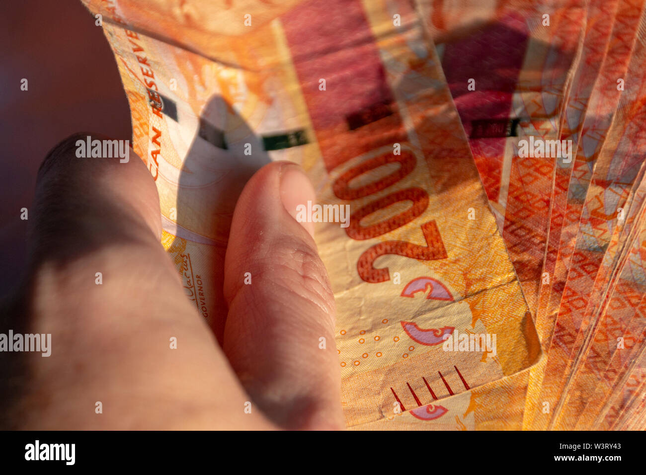 A close up view of a hand holding two hundred south african notes in a pile on a isolated black background - Stock Image